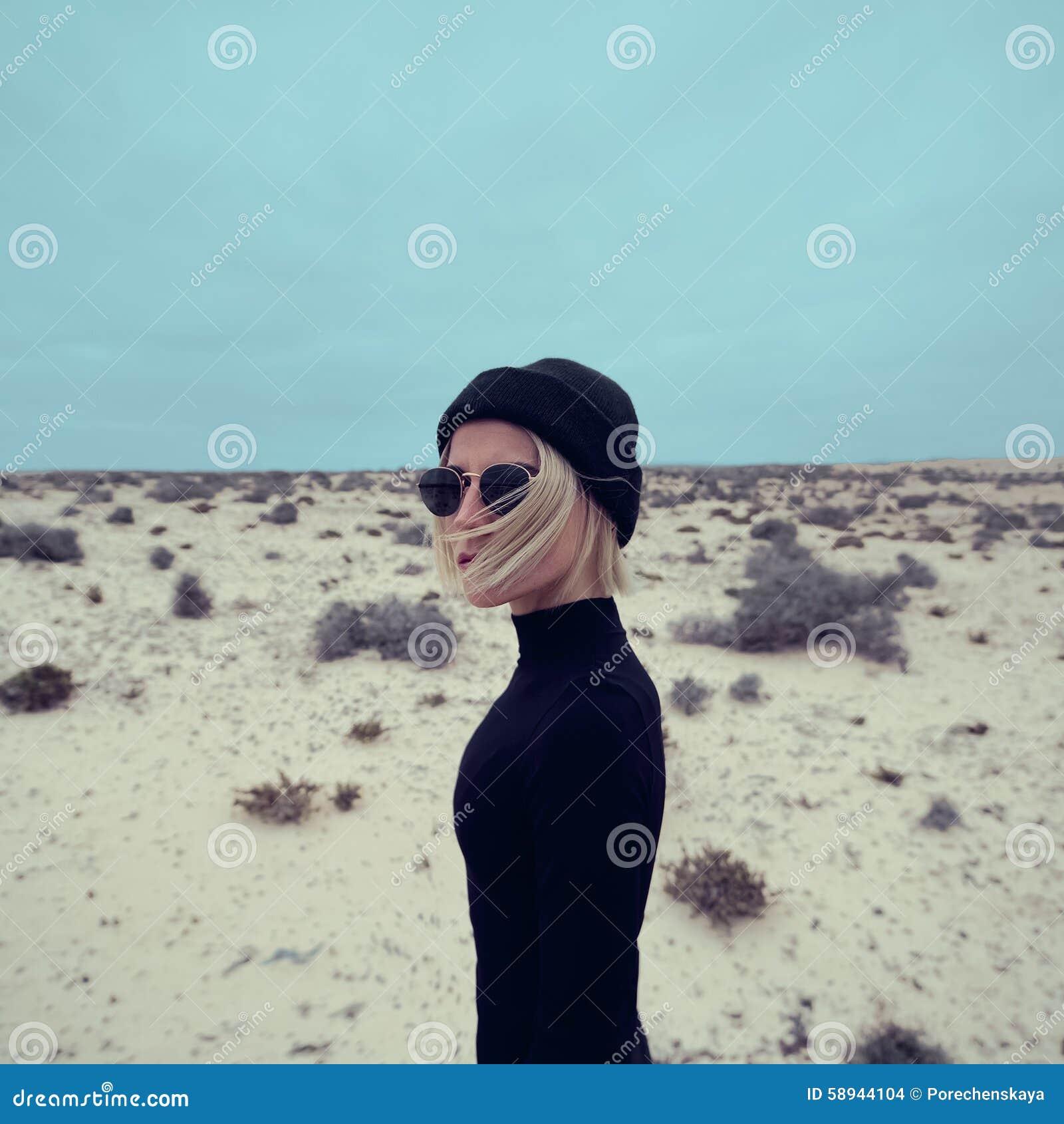 Elegancka dziewczyna w czerni sukni na tle pustynia