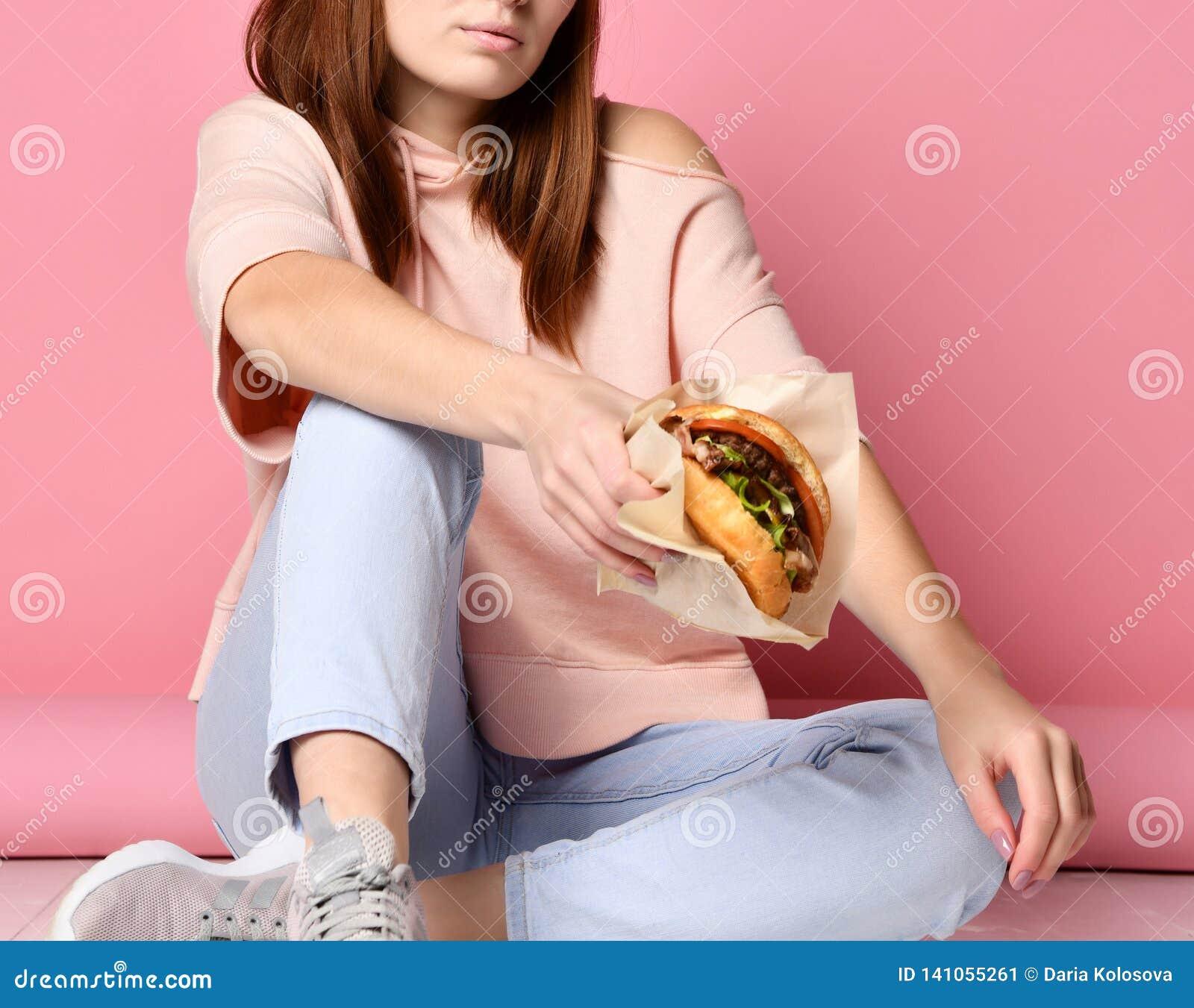Elegancka i młoda imbirowa kobieta chwyta hamburgeru kanapka na różowym tle