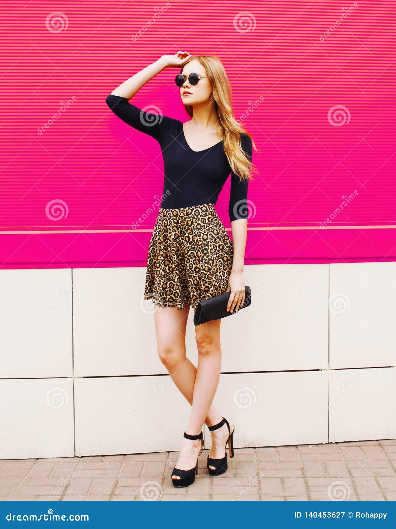Elegancka młoda blondynki kobieta w lampart spódnicie, okulary przeciwsłoneczni z torebki sprzęgłowy pozować na miasto ulicie