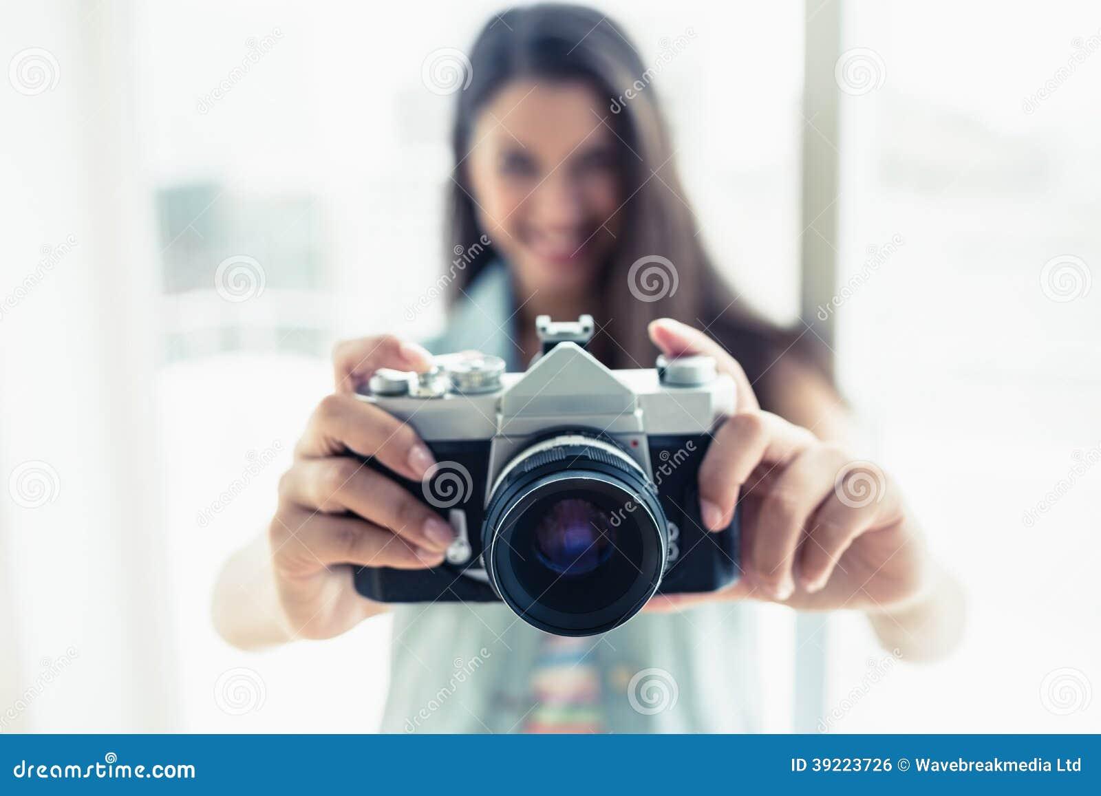 Elegancka młoda kobieta bierze fotografię przy kamerą