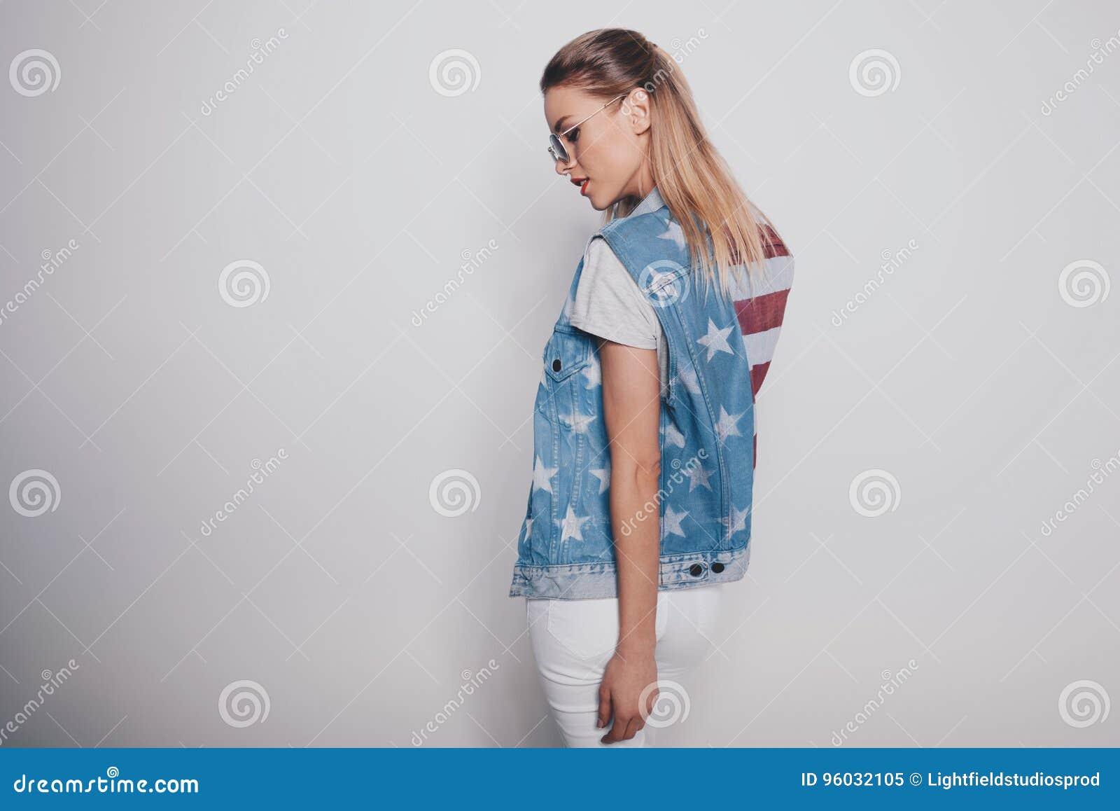 Elegancka modniś blondynki dziewczyna w amerykańskim patriotycznym stroju i okularach przeciwsłonecznych odizolowywających na pop
