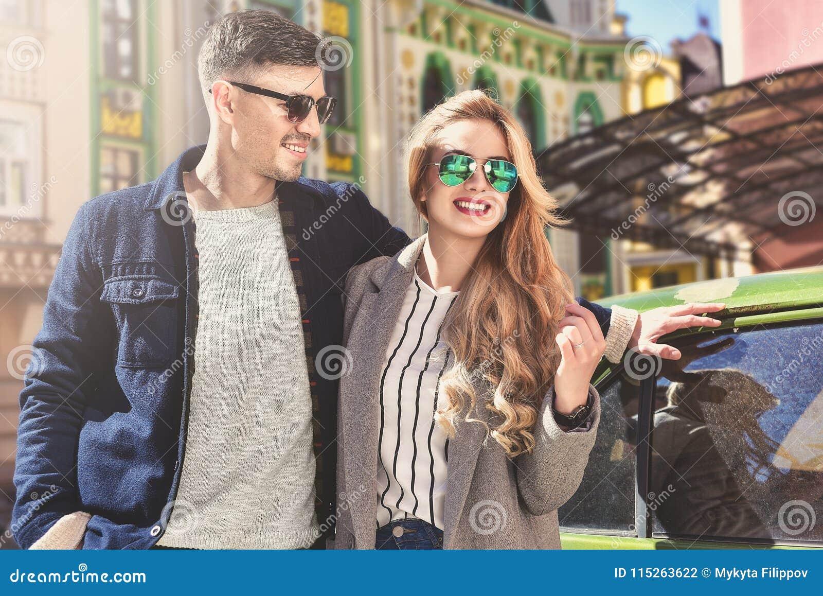 Elegancka para w okularach przeciwsłonecznych zostaje przy ulicą blisko samochodu