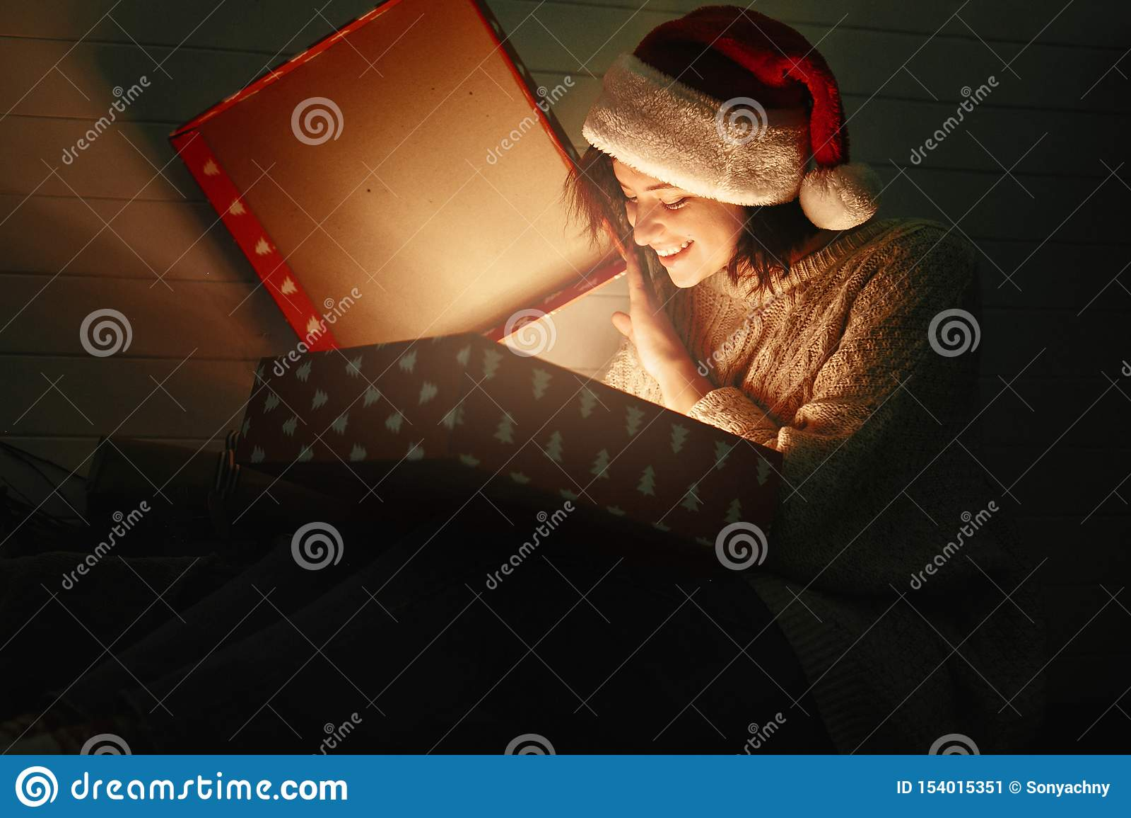 Elegancka szczęśliwa dziewczyna w Santa kapeluszu i wygodny puloweru otwarcia bożych narodzeń prezenta pudełko z magią zaświecamy
