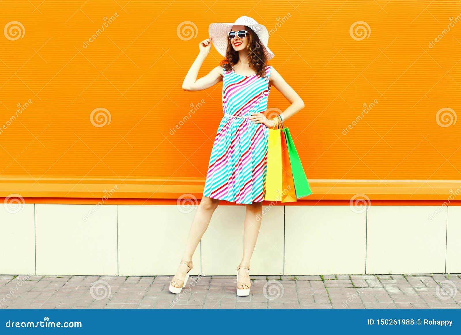 Elegancka uśmiechnięta kobieta jest ubranym kolorową pasiastą suknię z torbami na zakupy, lato słomiany kapelusz pozuje na pomara