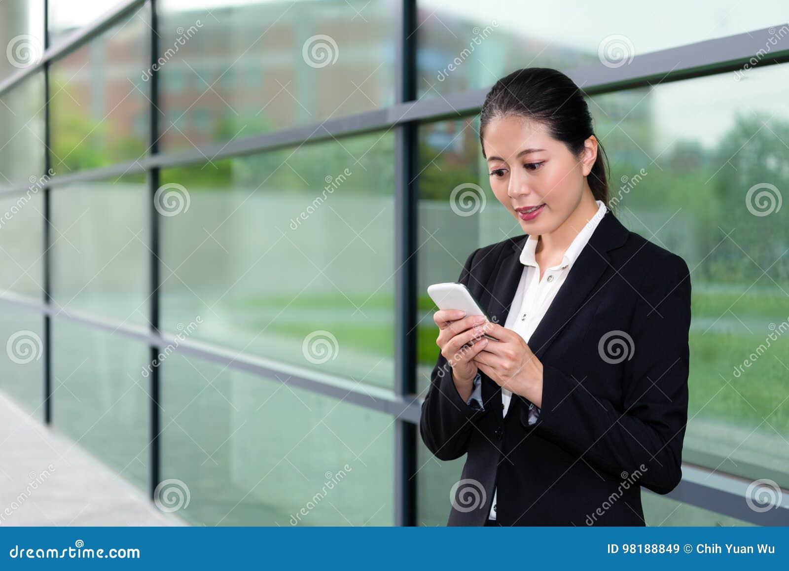 Elegancka urzędnik dziewczyna używa mobilnego telefon komórkowego