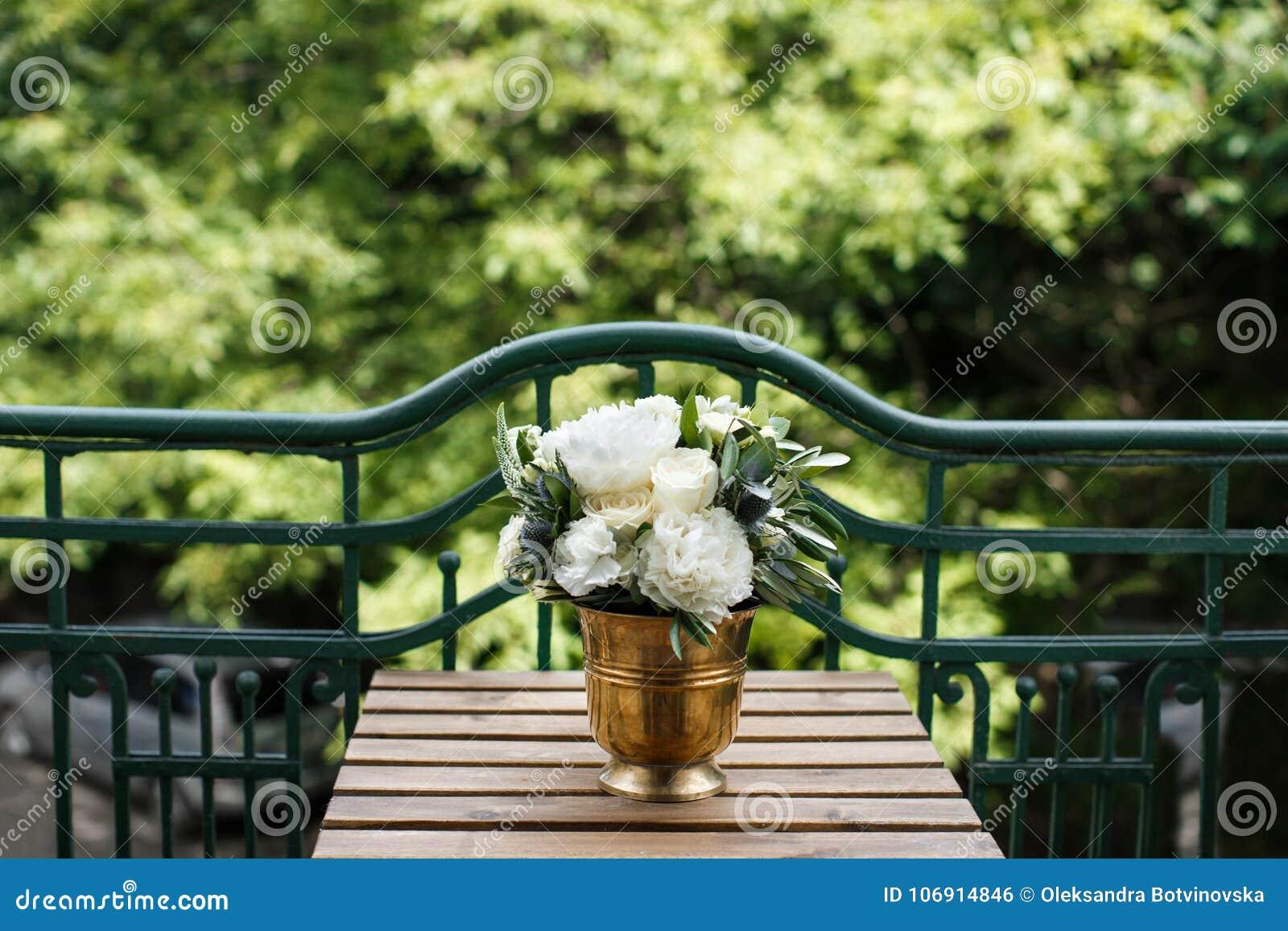 Elegancki ślubny bukiet na drewnianej ławce