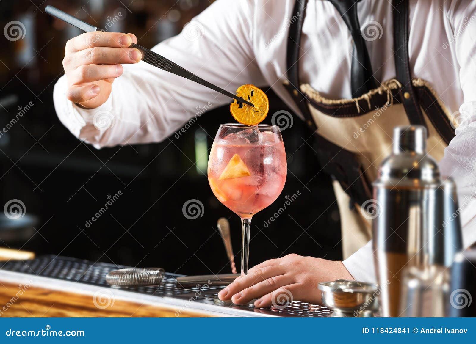 Elegancki barman robi różowemu koktajlu mieniu pomarańczowym układom scalonym