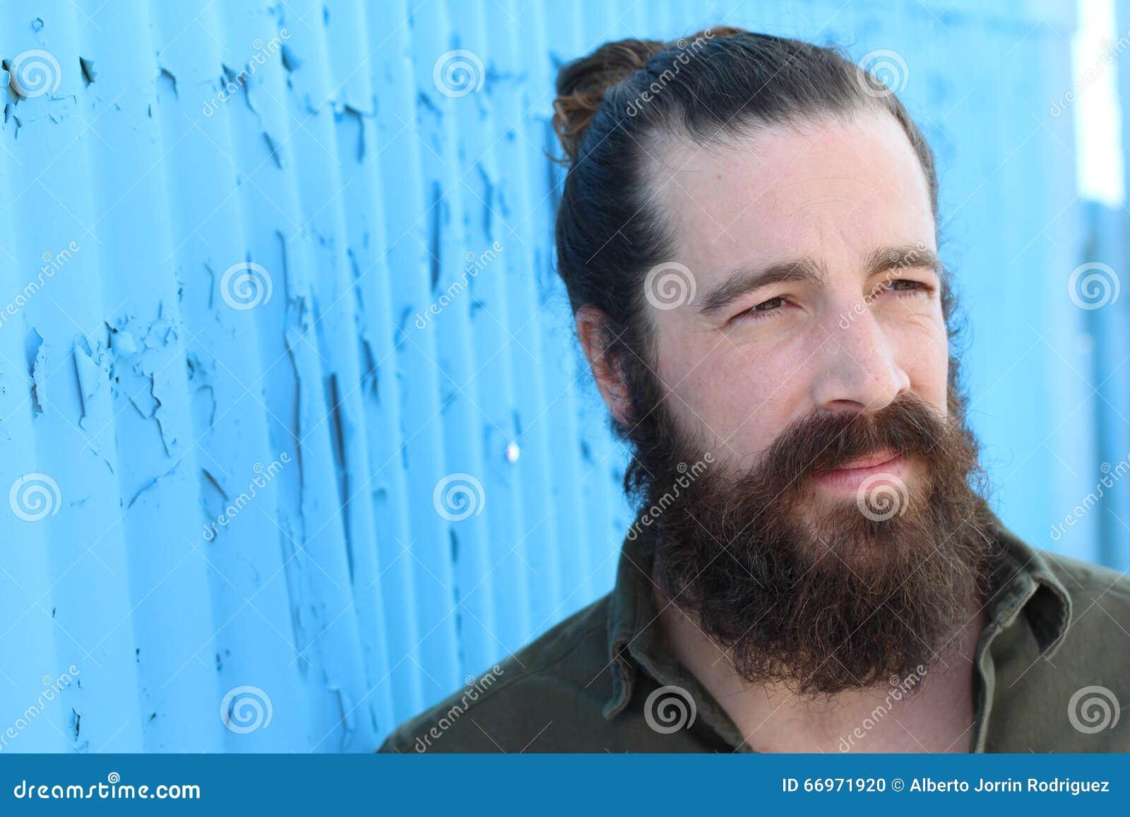 Elegancki brodaty modnisia model z mężczyzna babeczki fryzurą, styl życia w ulicie, głębia pole niebieska tła