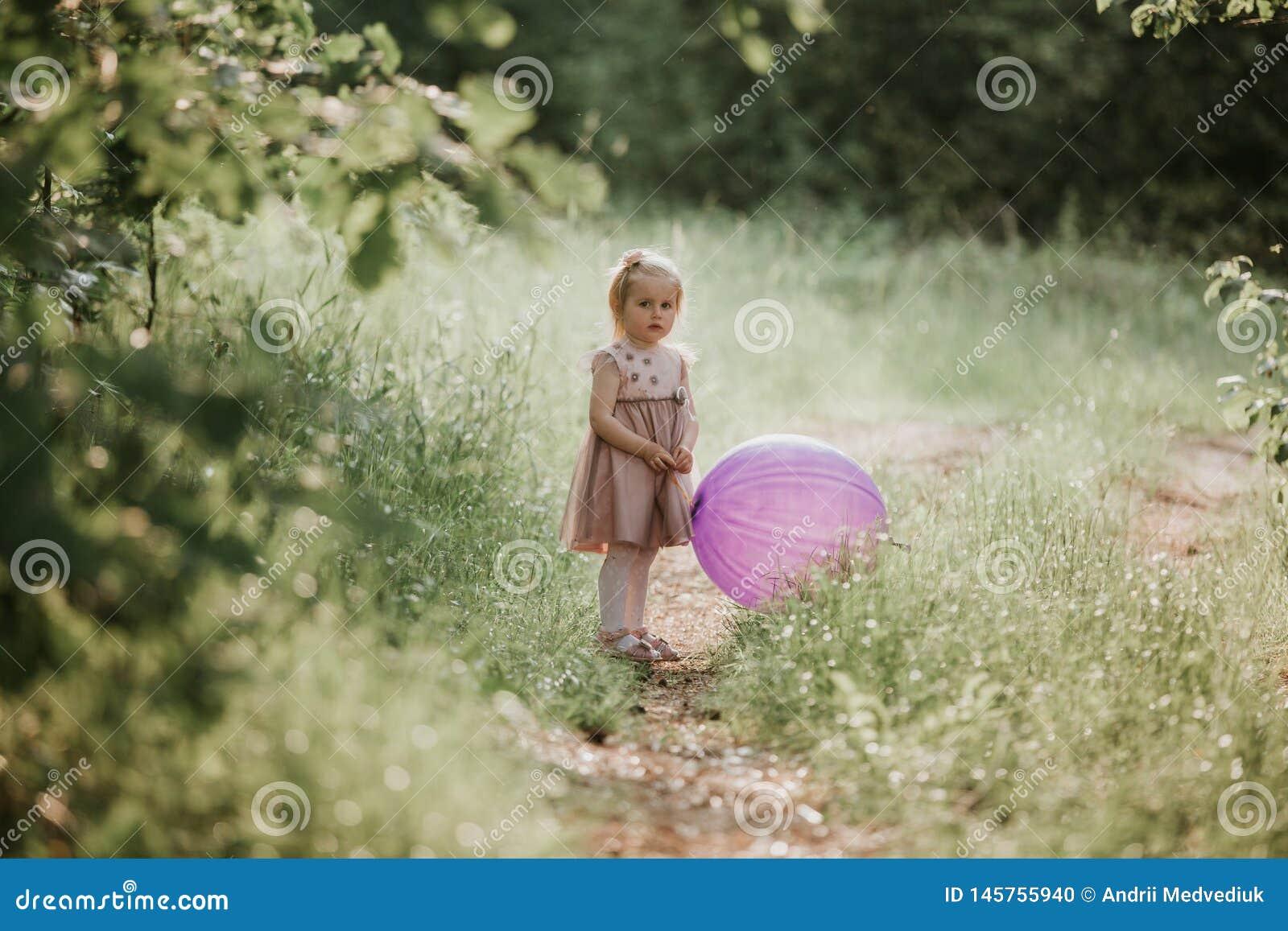 Elegancki dziewczynki 2-5 roczniak trzyma du?ego balon jest ubranym modne menchie ubiera w ??ce figlarnie