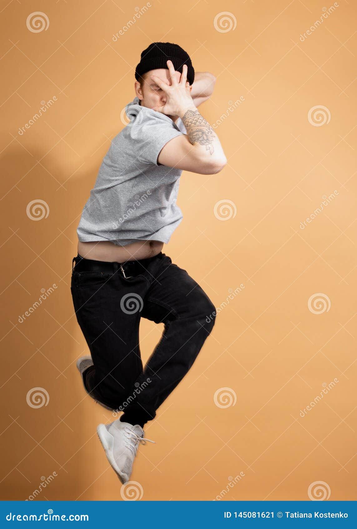 Elegancki facet ubierający w szarej koszula, czarnych cajgach i czarnym kapeluszu z tatuażem na jego ręce, skacze na beżu