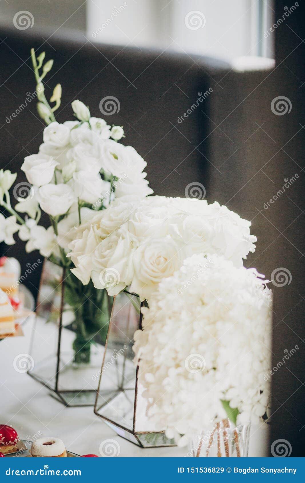 Elegancki kwiecisty wystrój na ślubu stole Białe róże i hortensja kwiaty w szklanej wazie na ślubnym centerpiece Luksusowy cateri