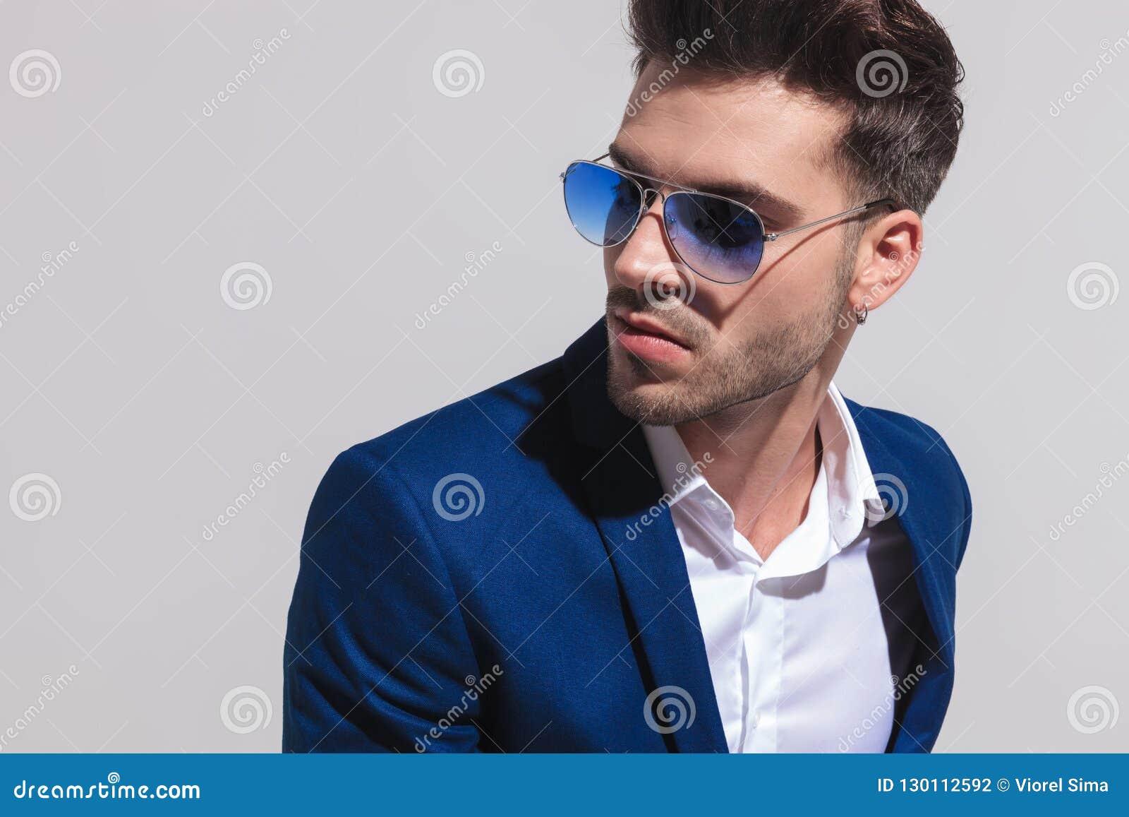 Elegancki mężczyzna patrzeje daleko od popierać kogoś w okularach przeciwsłonecznych