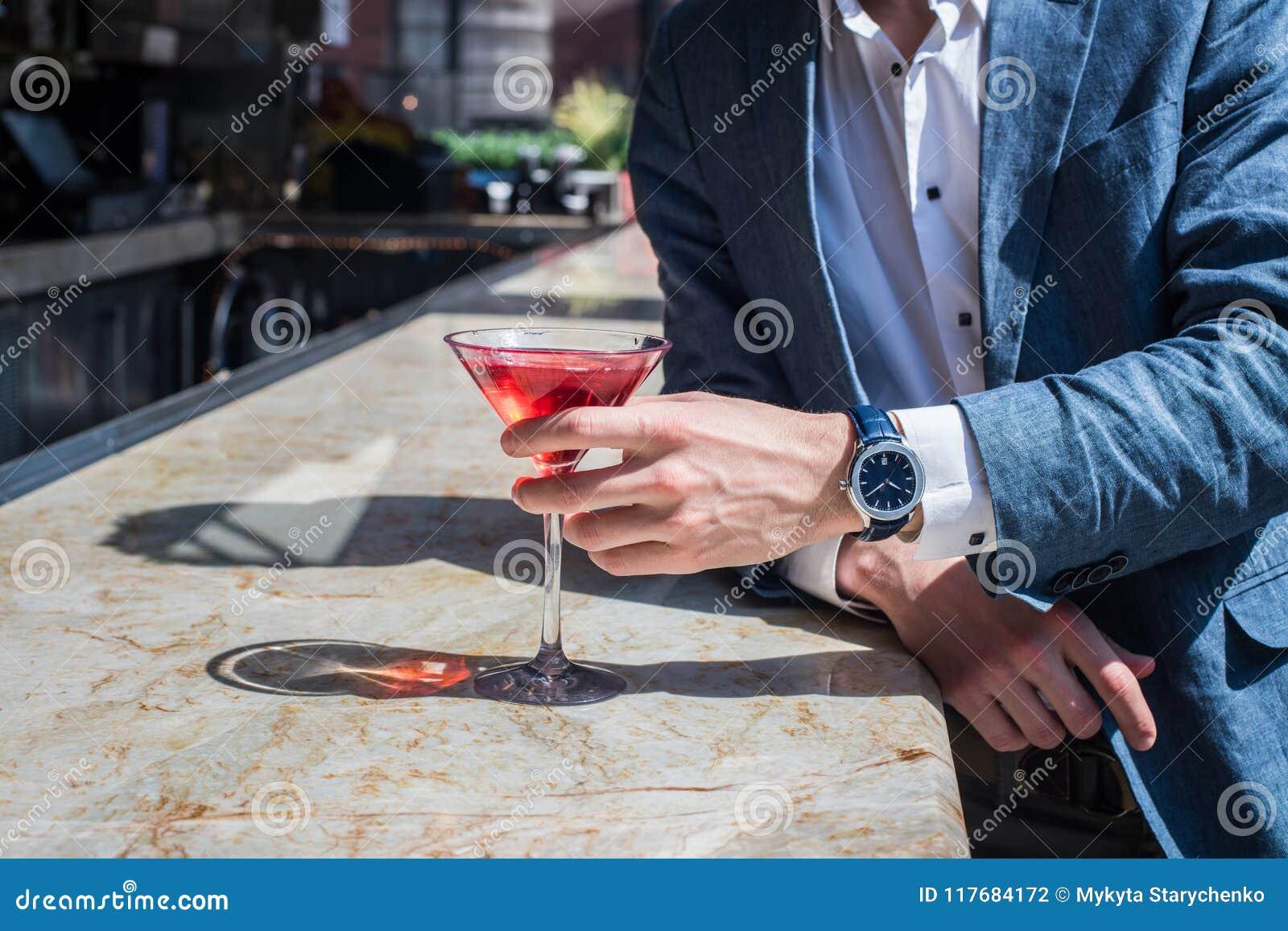 Elegancki mężczyzna pije koktajle na zakazuje kontuar i czekać do teraz dziewczyny