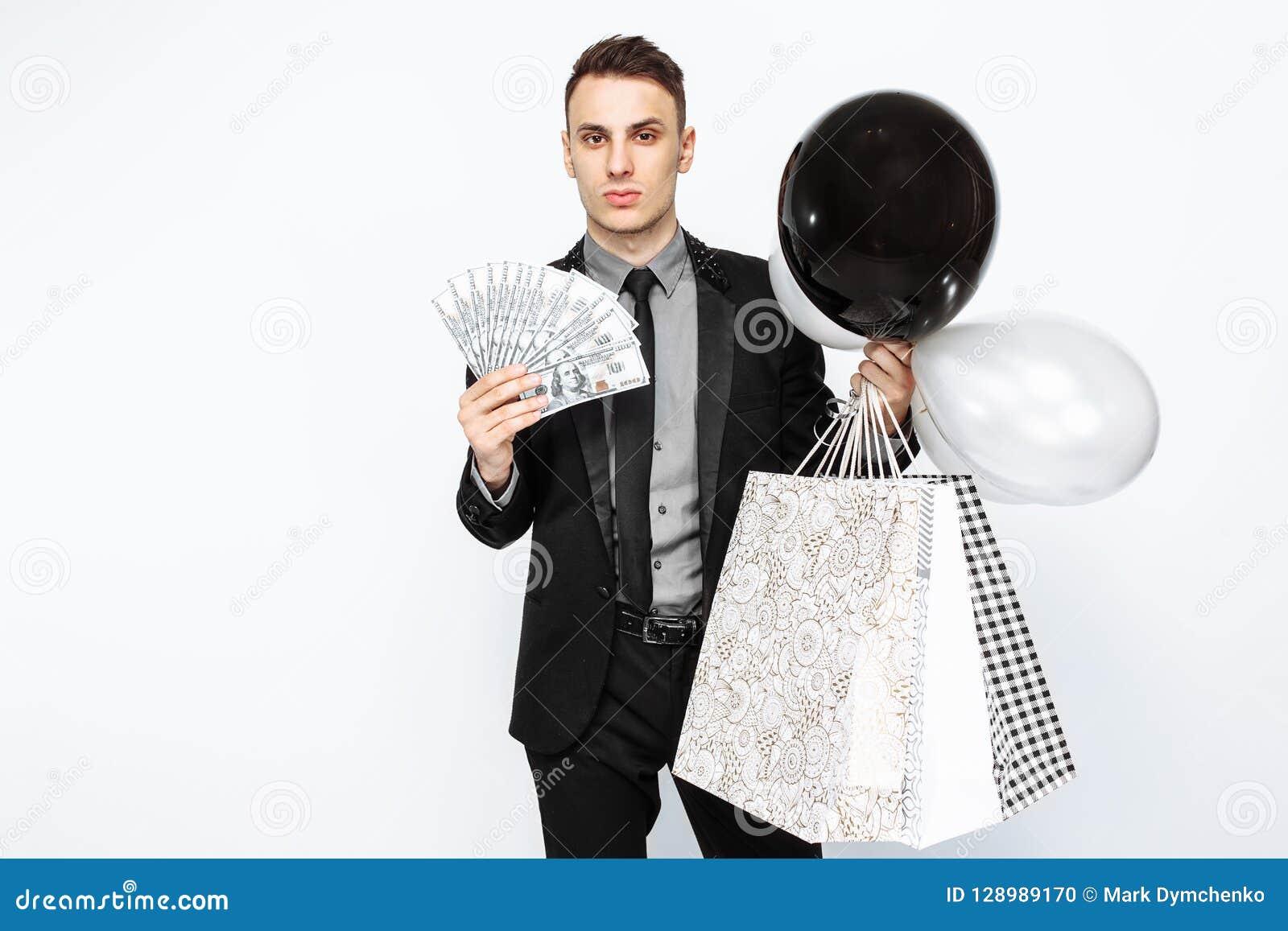 Elegancki mężczyzna w czarnym kostiumu, trzyma torby, dla robić zakupy, i