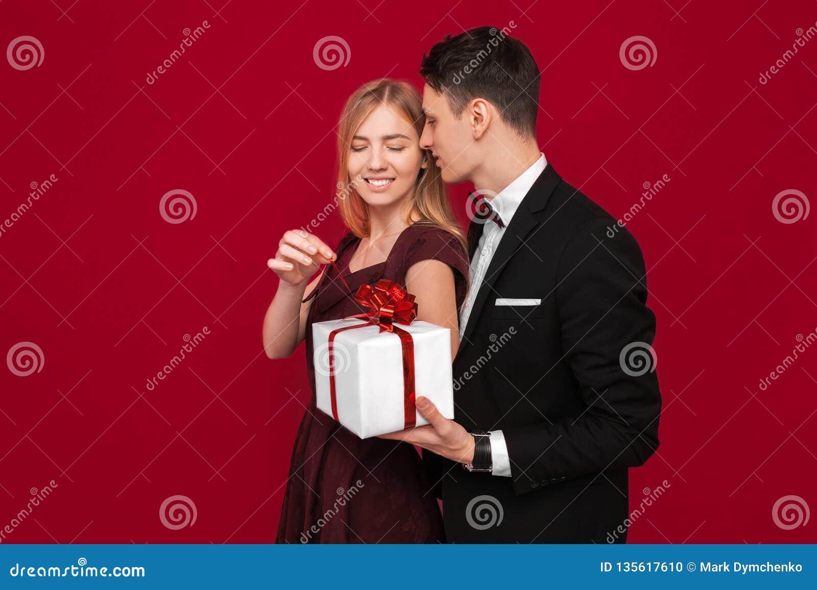 Elegancki mężczyzna w kostiumu daje niespodziance kobieta, daje ona prezentowi na czerwonym tle pojęcie kobieta dzień