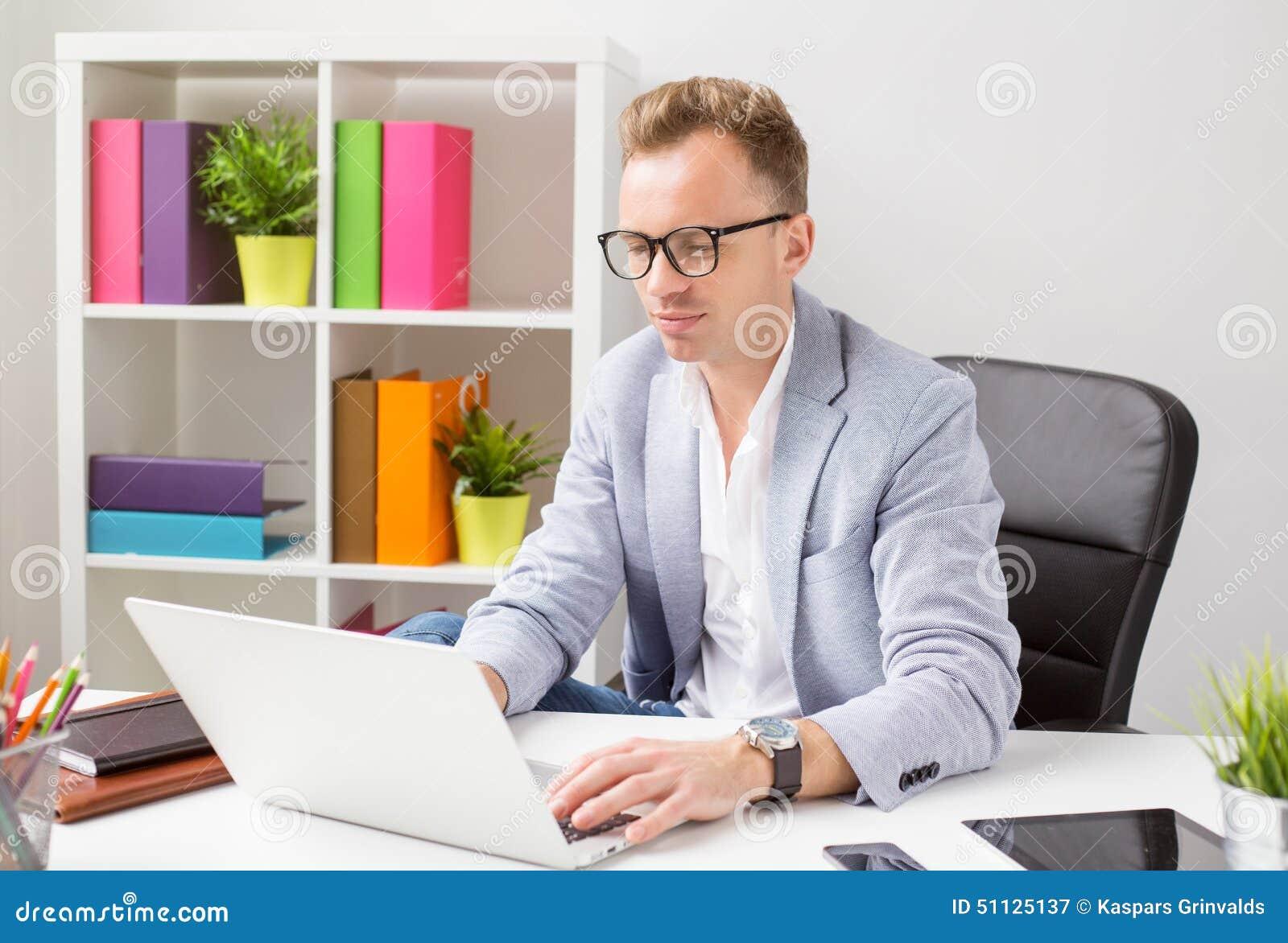 Elegancki młody człowiek pracuje z komputerem w biurze