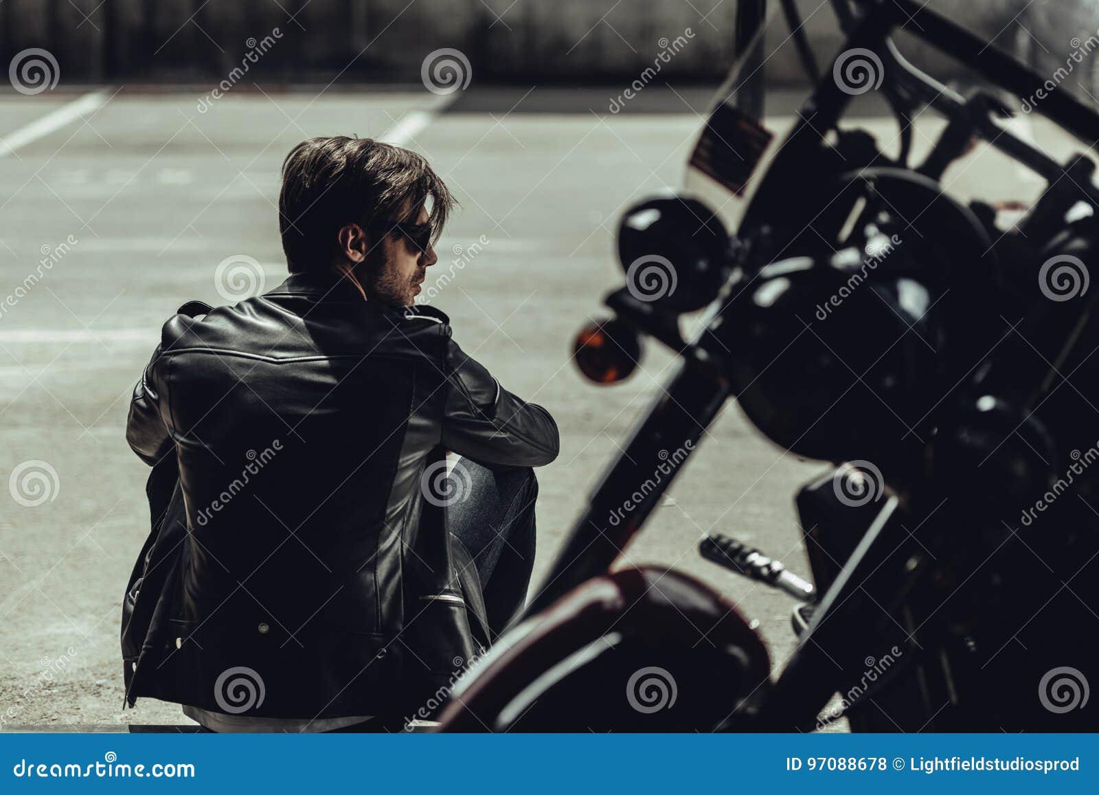 Elegancki młody człowiek siedzi blisko motocyklu i patrzeje daleko od w skórzanej kurtce