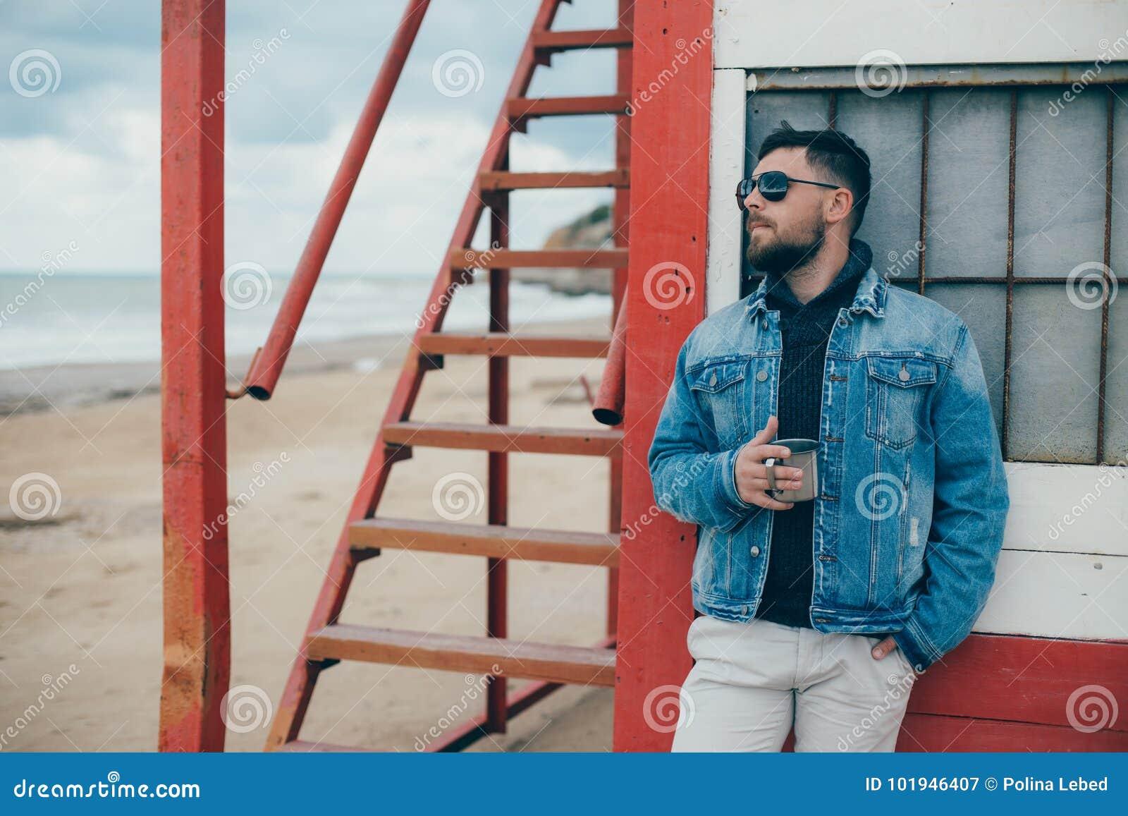 Elegancki młody człowiek stoi blisko oceanu z filiżanką herbata z brodą