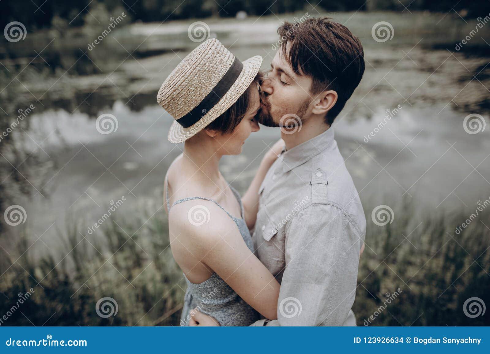 Elegancki modniś pary całowanie przy jeziorem mężczyzna i kobiety obejmowanie,