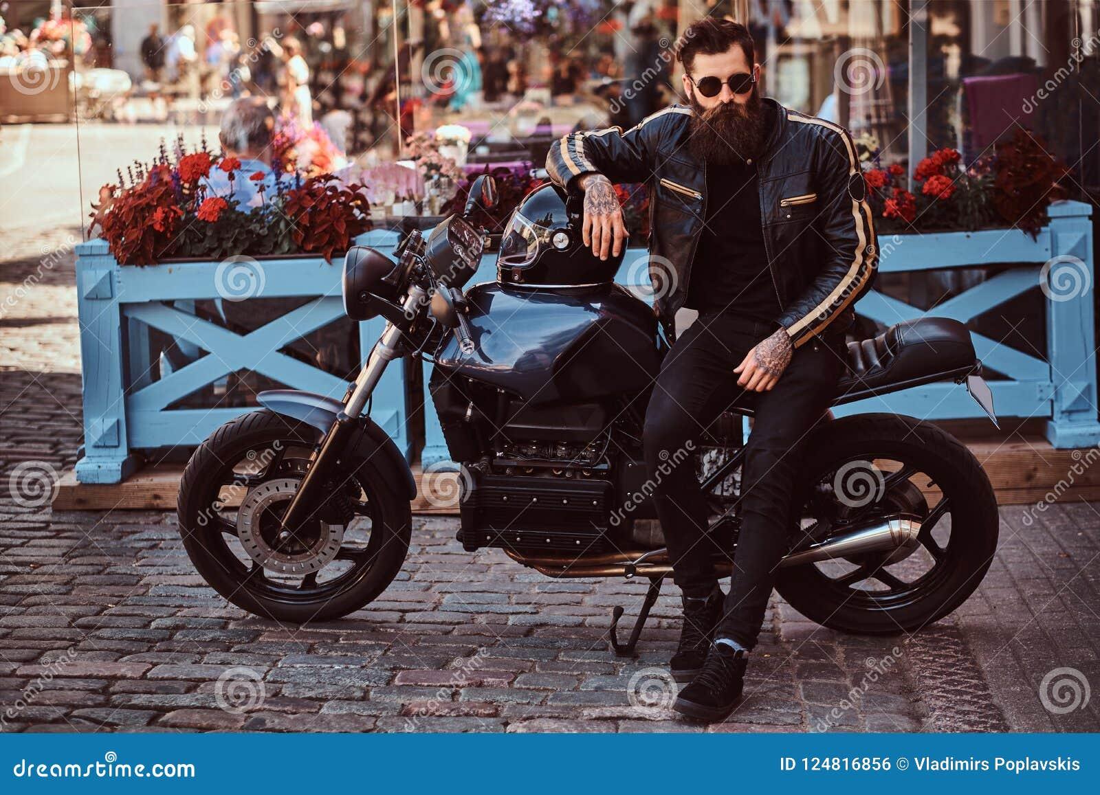 Elegancki modny rowerzysta w okularach przeciwsłonecznych ubierał w czarnej skórzanej kurtce, siedzi na jego na zamówienie retro