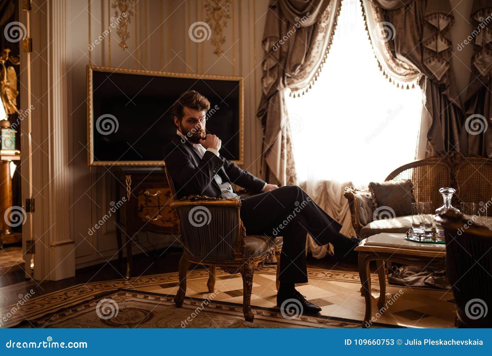 Elegancki pomyślny biznesmen w formalnym czarnym kostiumu, siedzi na krześle w królewskim pokoju, odczucia relaksujący, poważny r