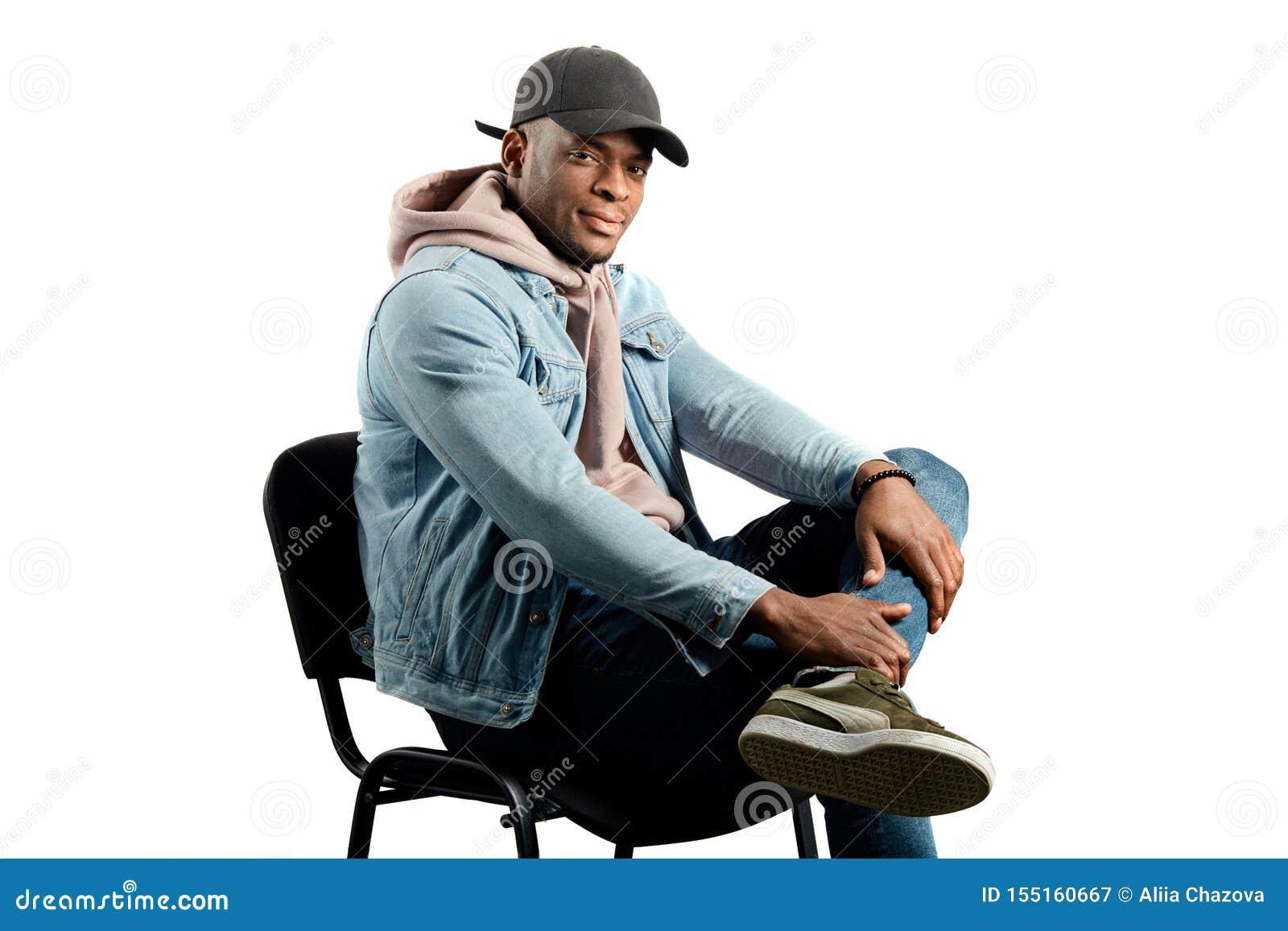 Elegancki samiec modela obsiadanie na krześle w studiu
