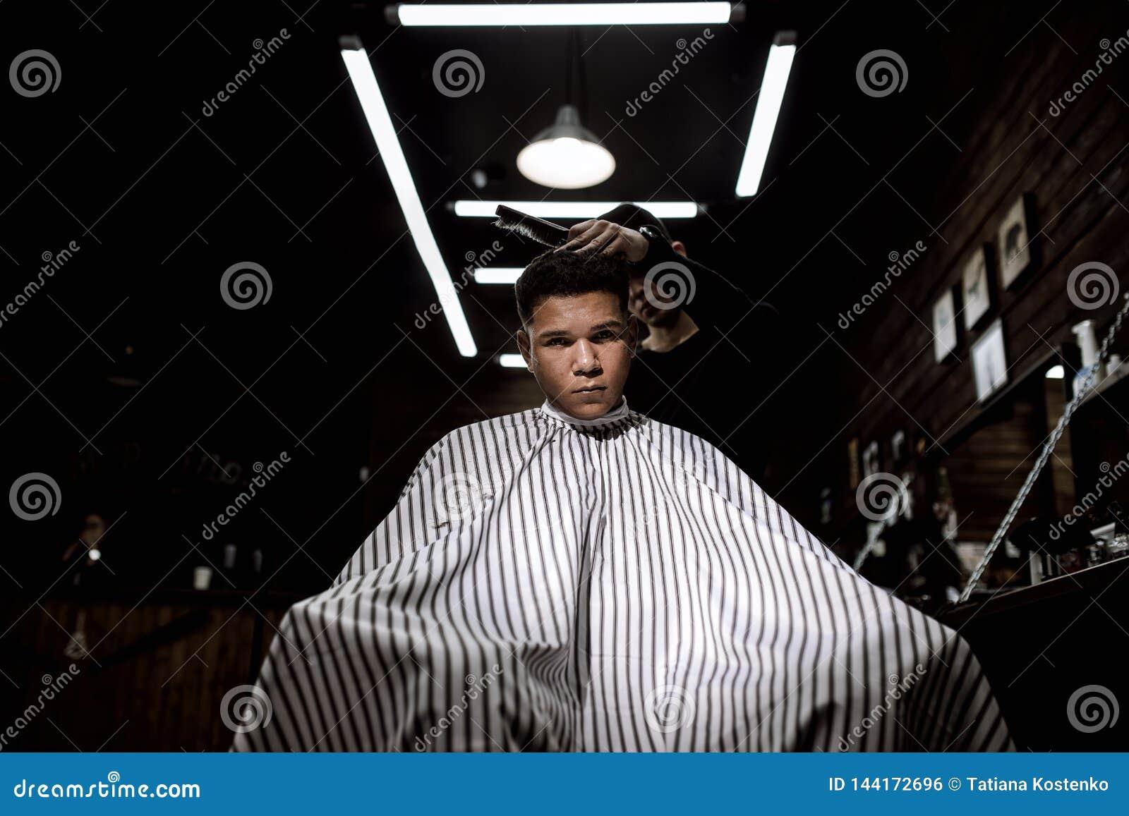 Elegancki zakład fryzjerski Moda fryzjer męski robi eleganckiej fryzurze dla czarnogłowego mężczyzny obsiadania w karle