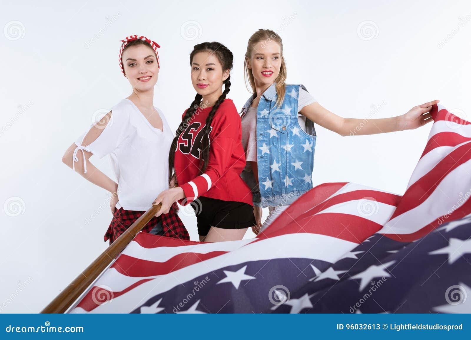 Eleganckie młode kobiety pozuje z flaga amerykańską w rękach