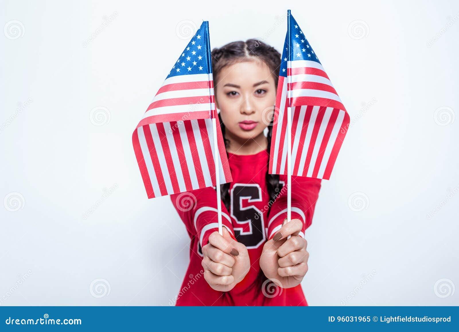 Eleganckiego modnisia azjatykcia dziewczyna trzyma małe flaga amerykańskie i patrzeje kamerę w czerwonej bluzie sportowa