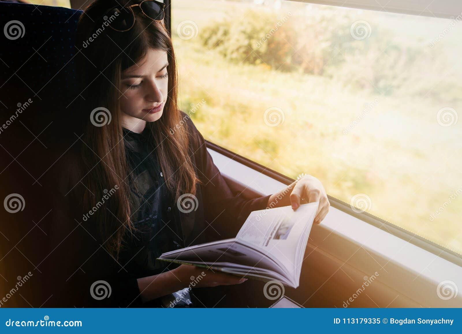 Eleganckiej modniś dziewczyny czytelnicza książka przy okno światłem w pociągu Trav