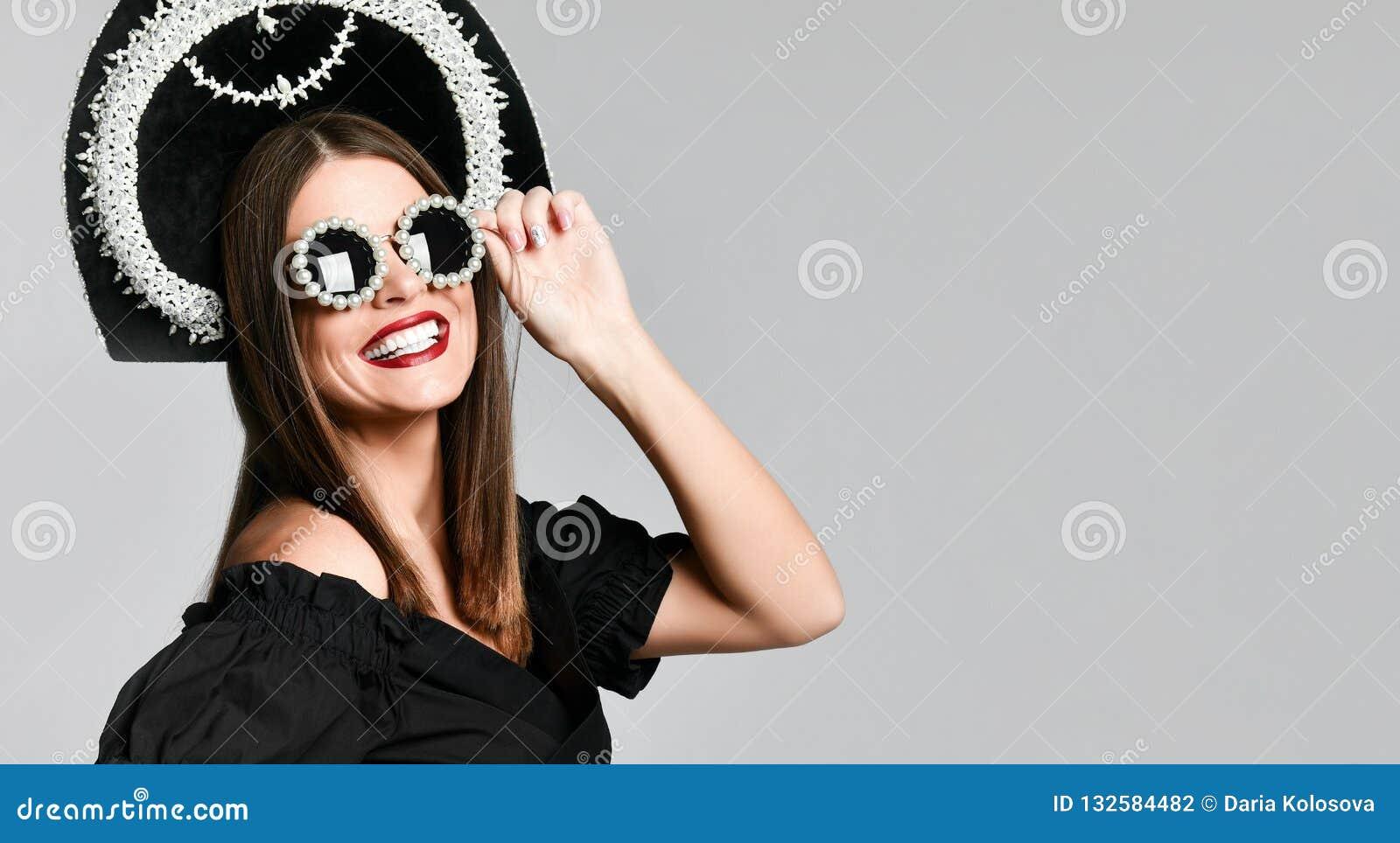 Elegans och utformar Studiostående av den ursnygga unga kvinnan i den lilla svarta klänningen som poserar mot gul bakgrund