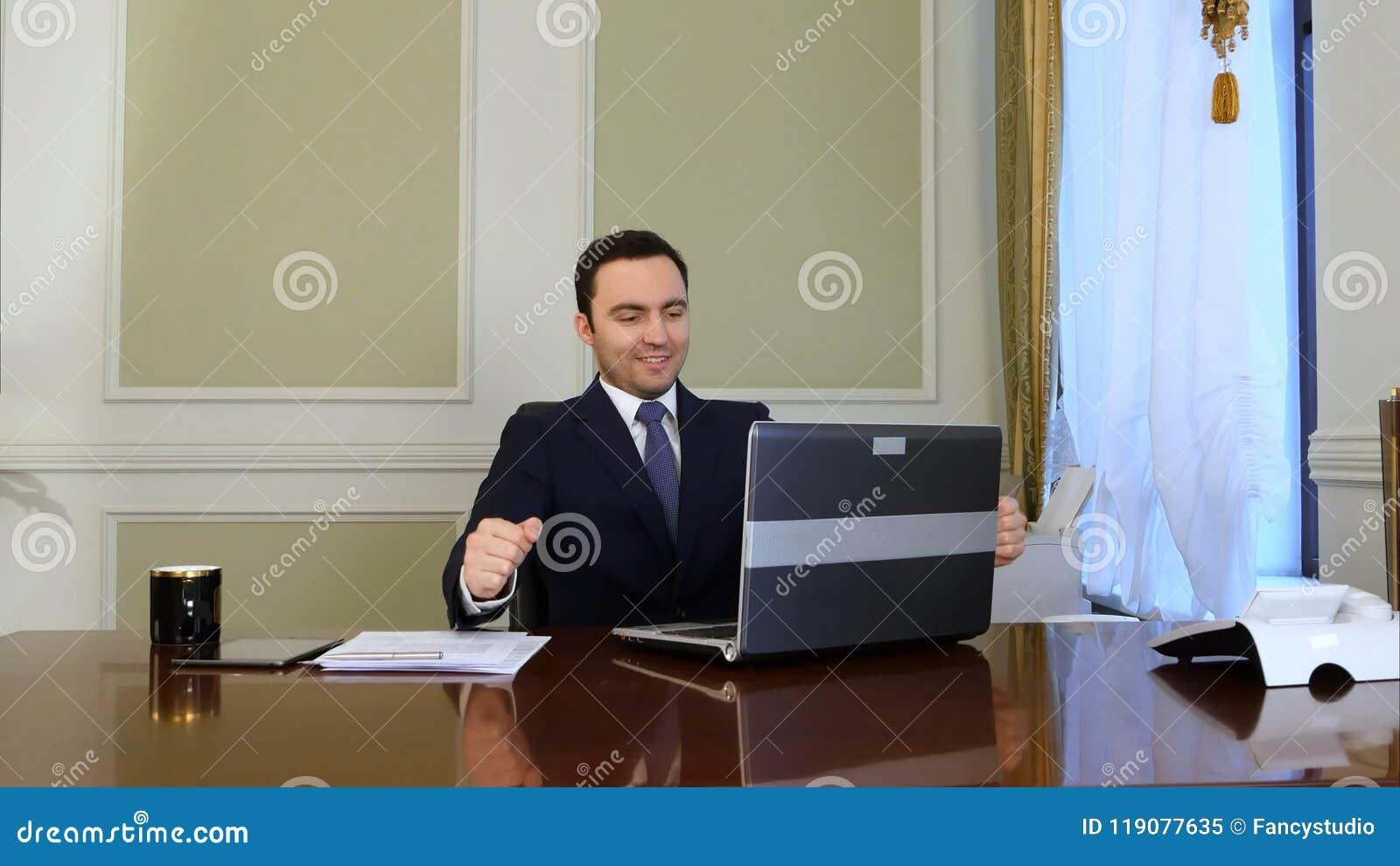 Elegant affärsman i den vita skjortan som korrigerar hans band och knäppas hans dräktomslag och arbeta för starter