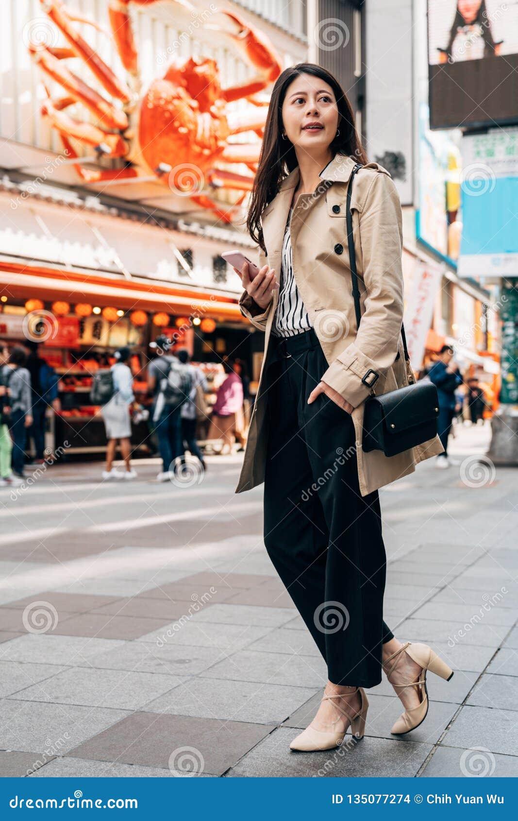 Elegant Asian girl using phone checking direction