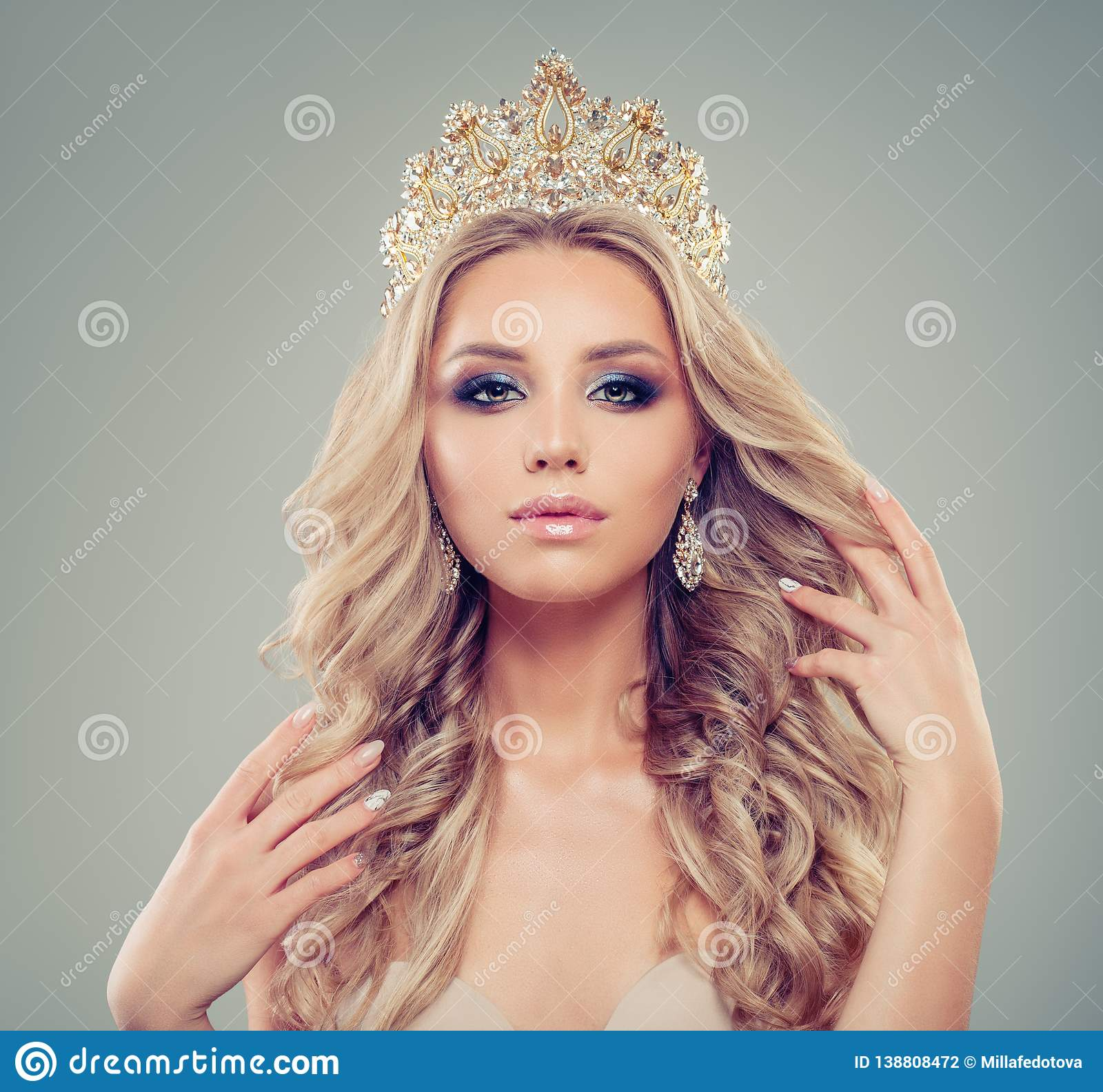 Elegant blonde woman with makeup, long healthy curly hairstyle, gold jewelry crown and earrings, portrait