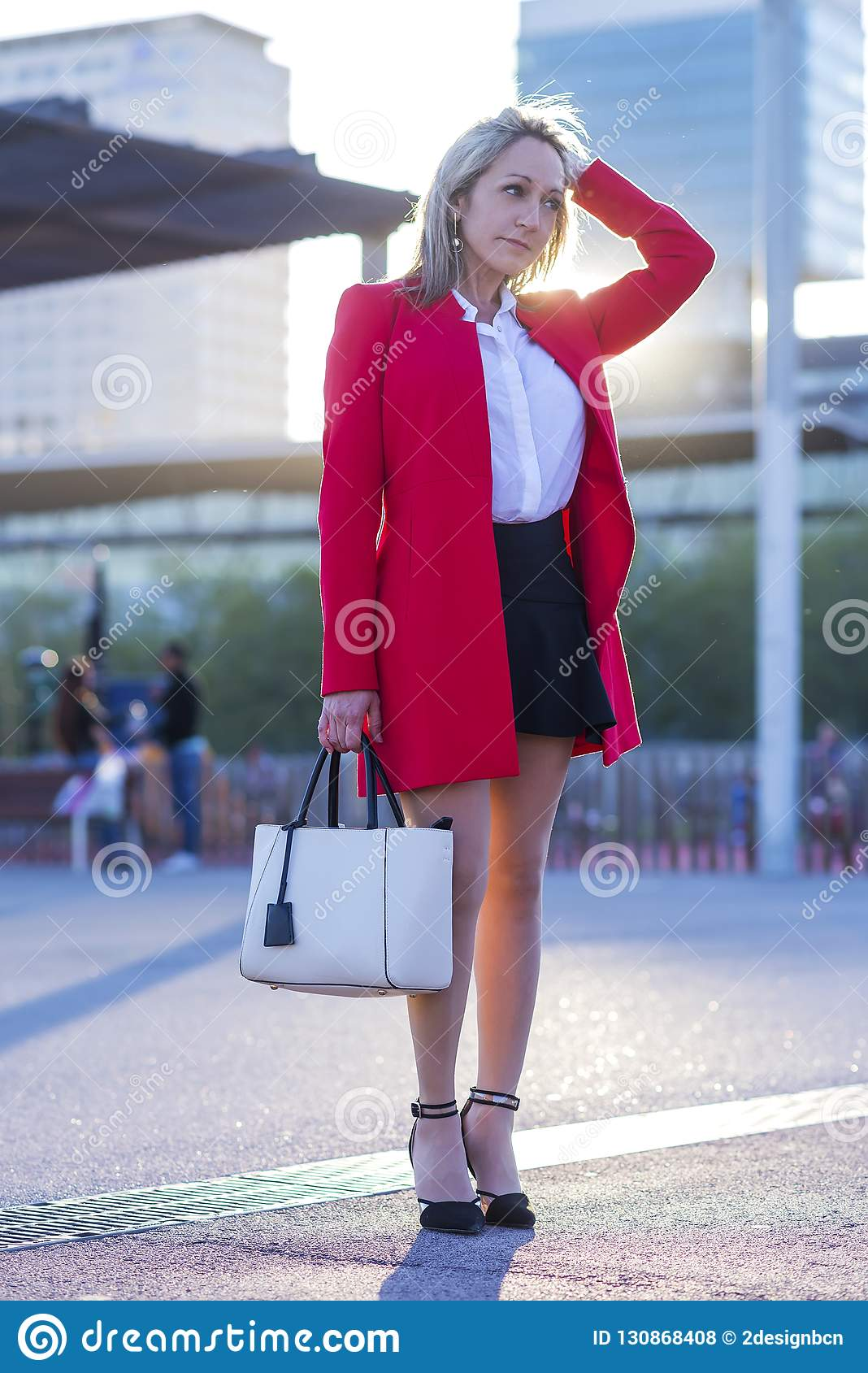 400273f27936 Elegant Blonde Woman Standing In The Street Wearing Red Jacket Stock ...