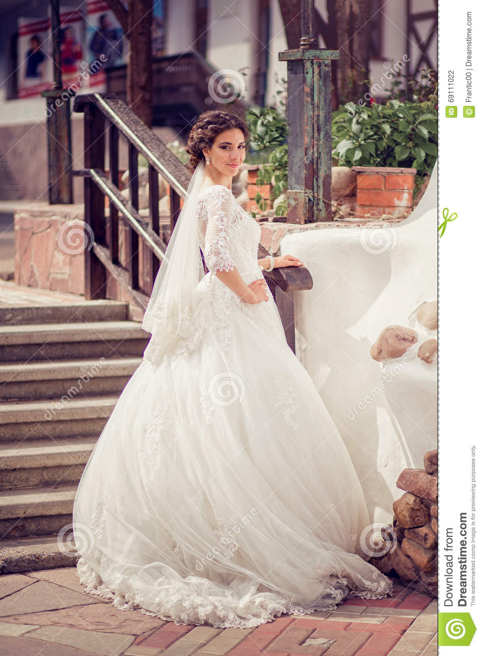Elegant Bride In Wedding Dress With Dipped Hem In Full Length On A