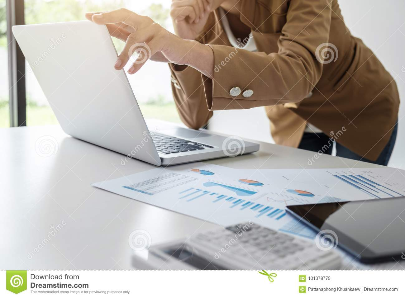 Elegant businesswoman leader working on laptop in a modern office, analyzing data and graph, using calculator calculate, young