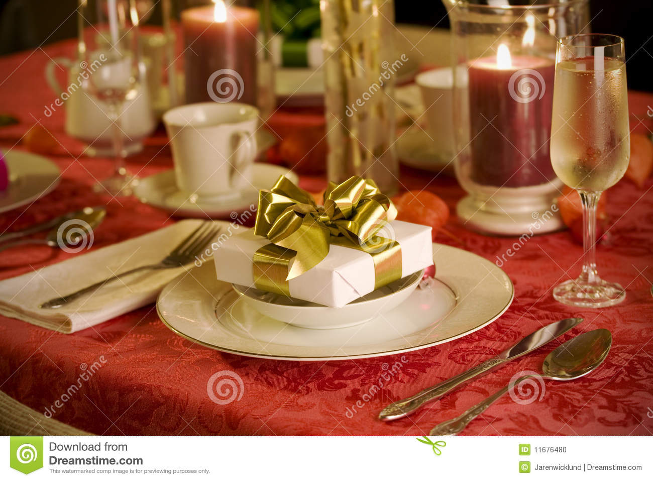 Elegant christmas table setting in red with gold gift as focal point