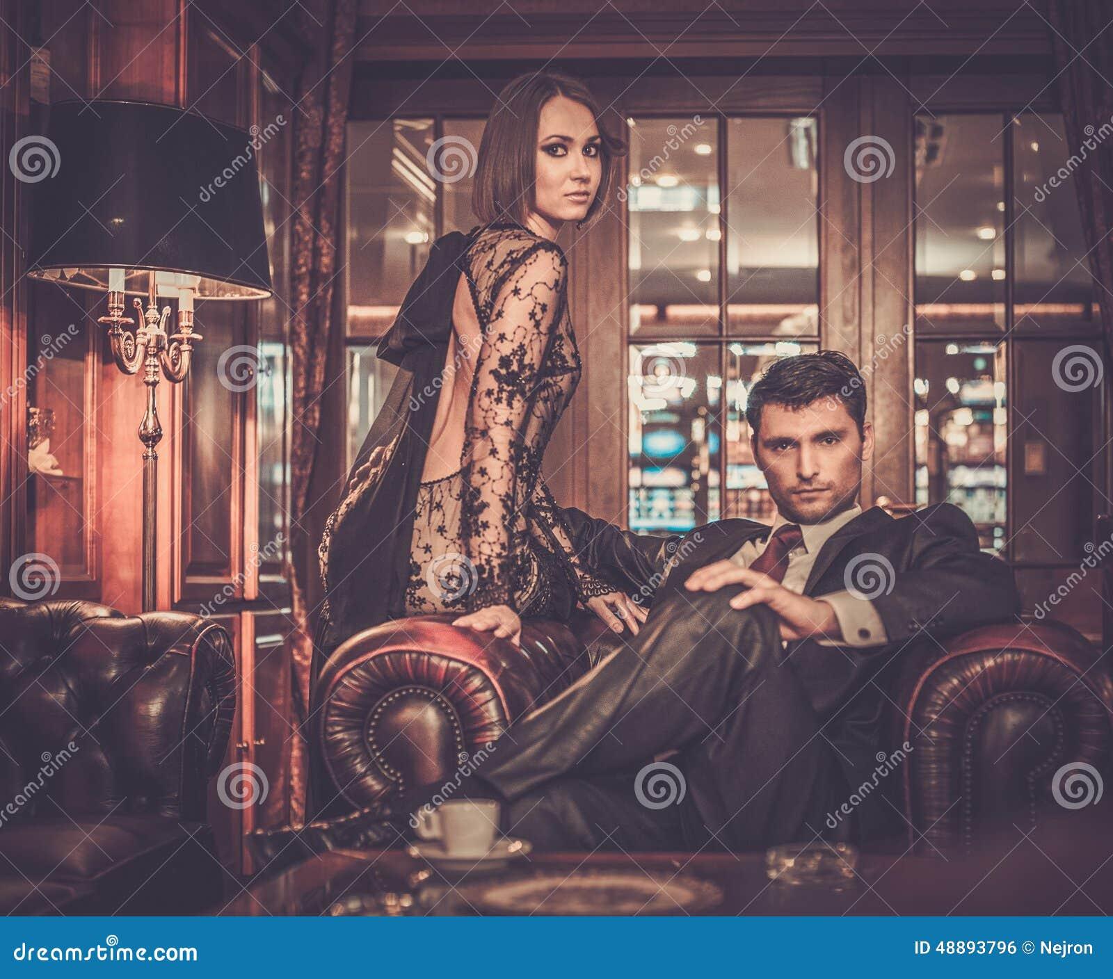 Elegant couple in luxury cabinet interior