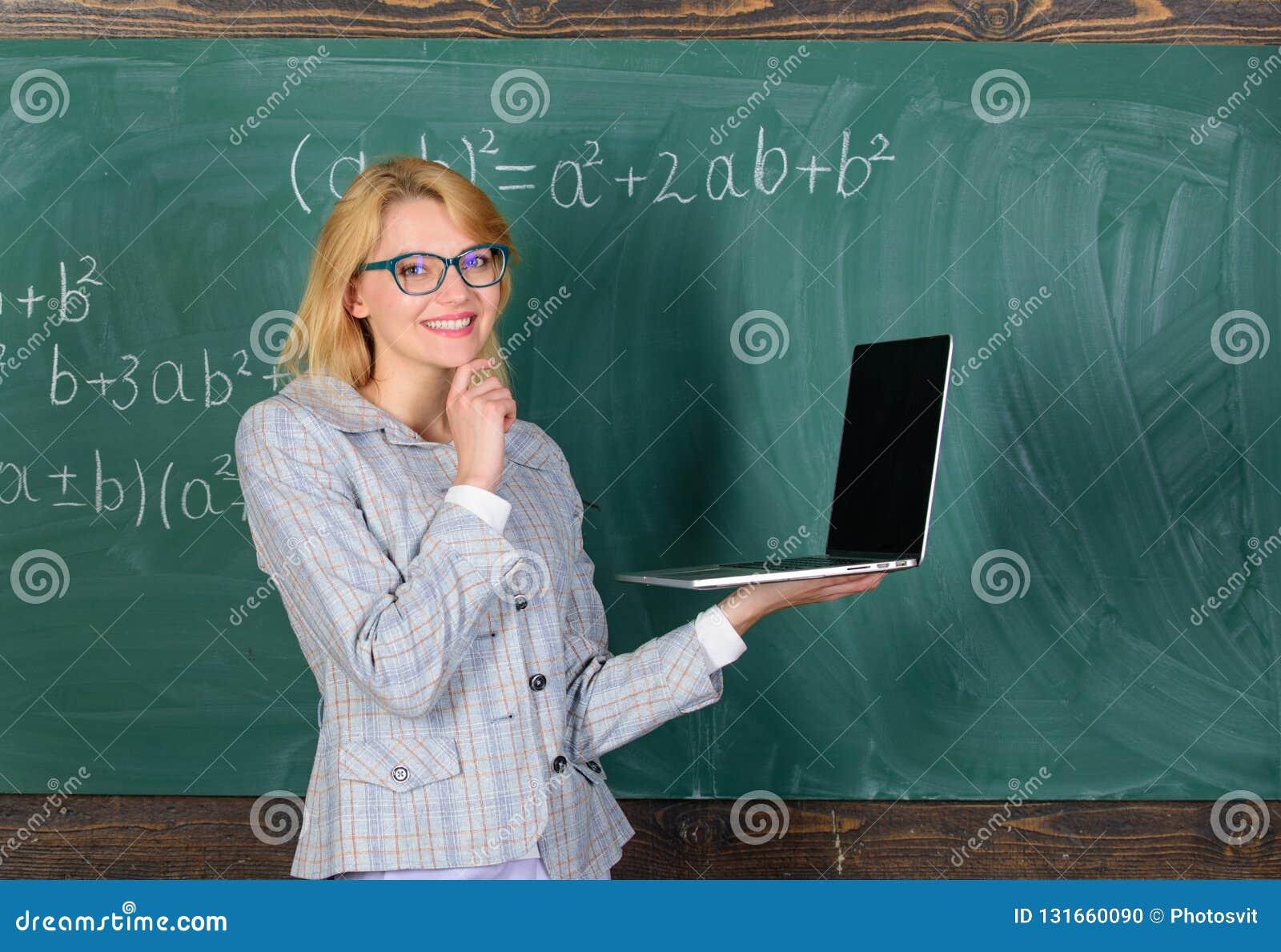 Elegant dam för lärare med den moderna bärbara datorn som surfar svart tavlabakgrund för internet