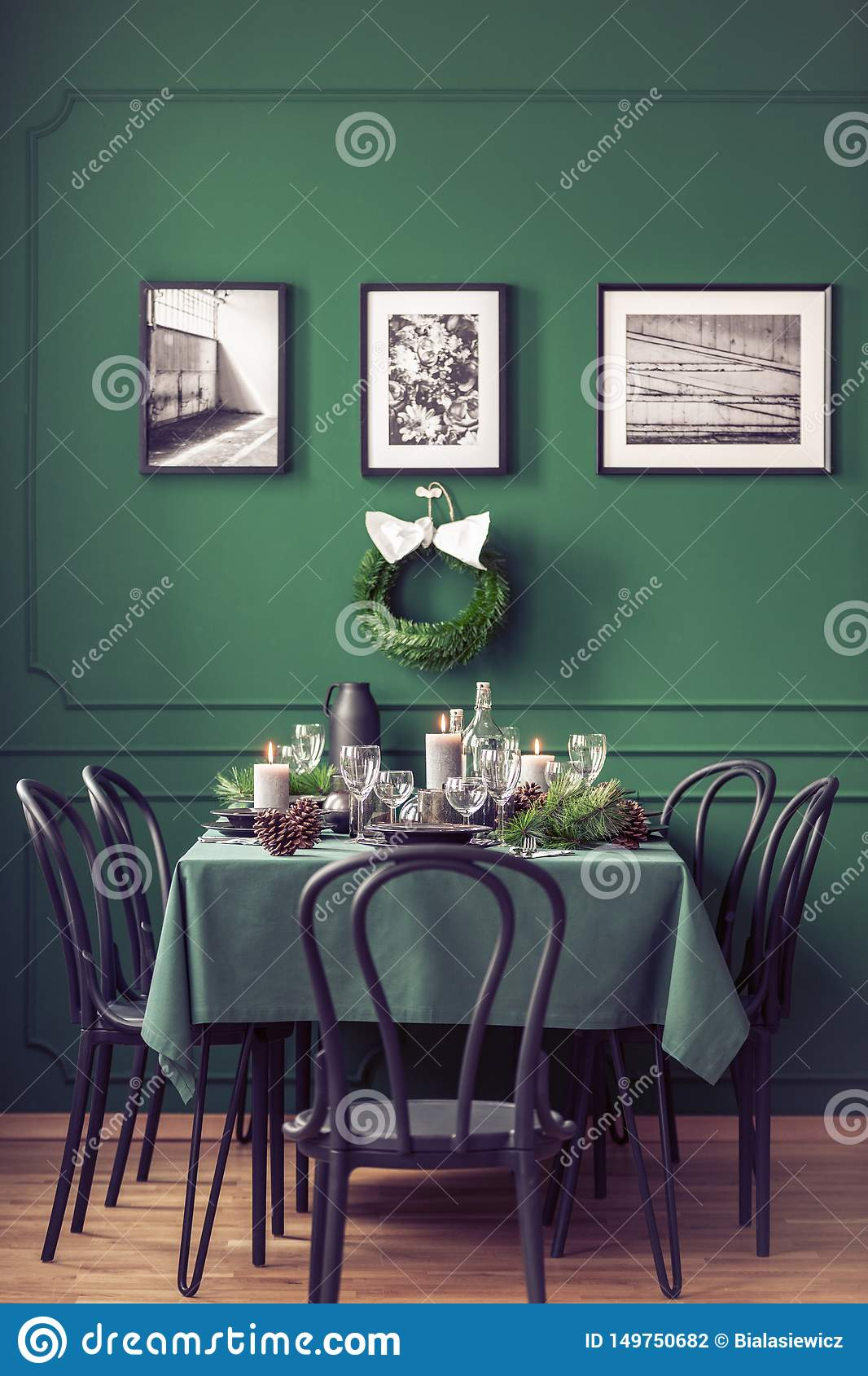 Elegant dining room table with wine glasses, plates and candles set for christmas dinner, gallery of black and white posters on