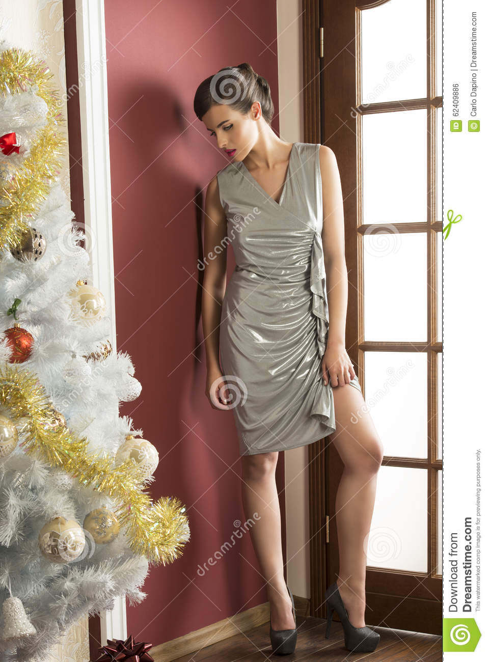 daefbc4d852b1 Pretty elegant brunette girl with silver dress, hair-style and heels posing  near decorated christmas tree. xmas time