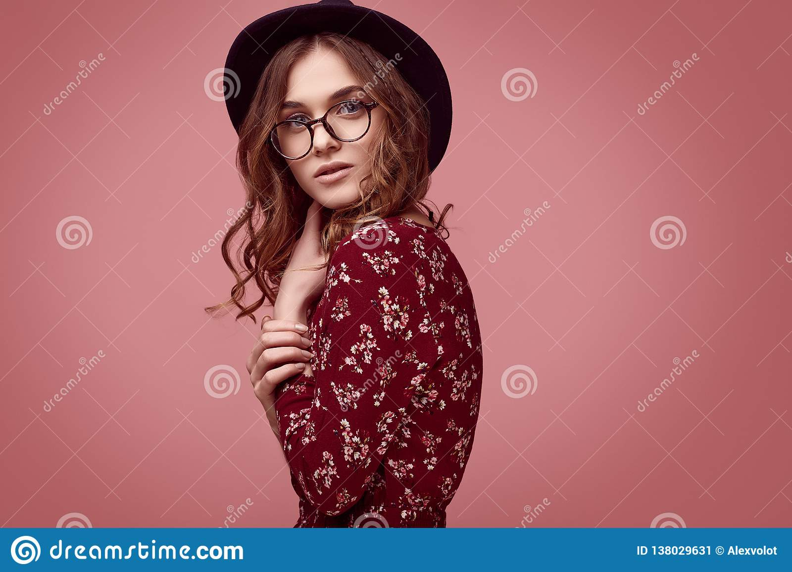 36968e6d28249 Sensual portrait of elegant glamor hipster girl in red fashion dress, black  hat and glasses posing on colorful pink background in studio