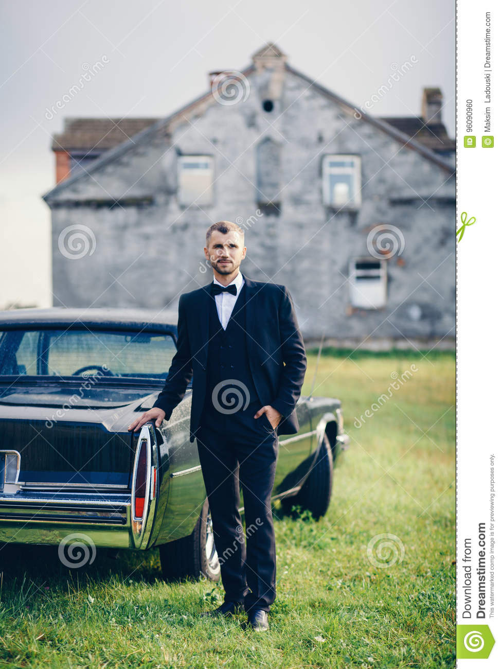 8c36e469d7e4 Handsome groom at wedding tuxedo smiling and waiting for bride near retro  car. Elegant groom in black costume and bow-tie