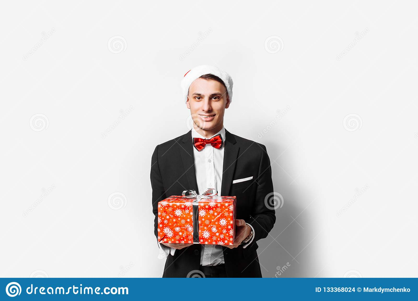 Elegant guy in the hat of Santa Claus with a Christmas gift in h