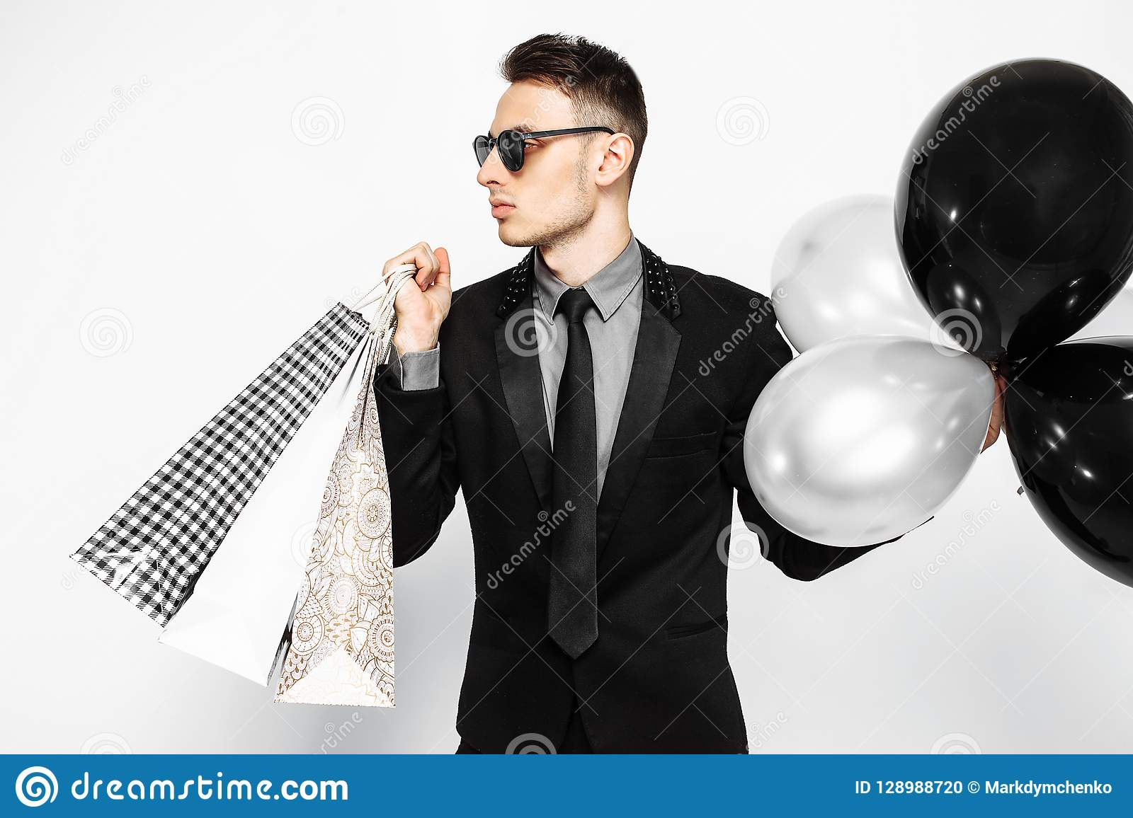 Elegant guy in sunglasses, black suit, holding bags, for shopping, and black balloons, on white background. Black Friday shopping,