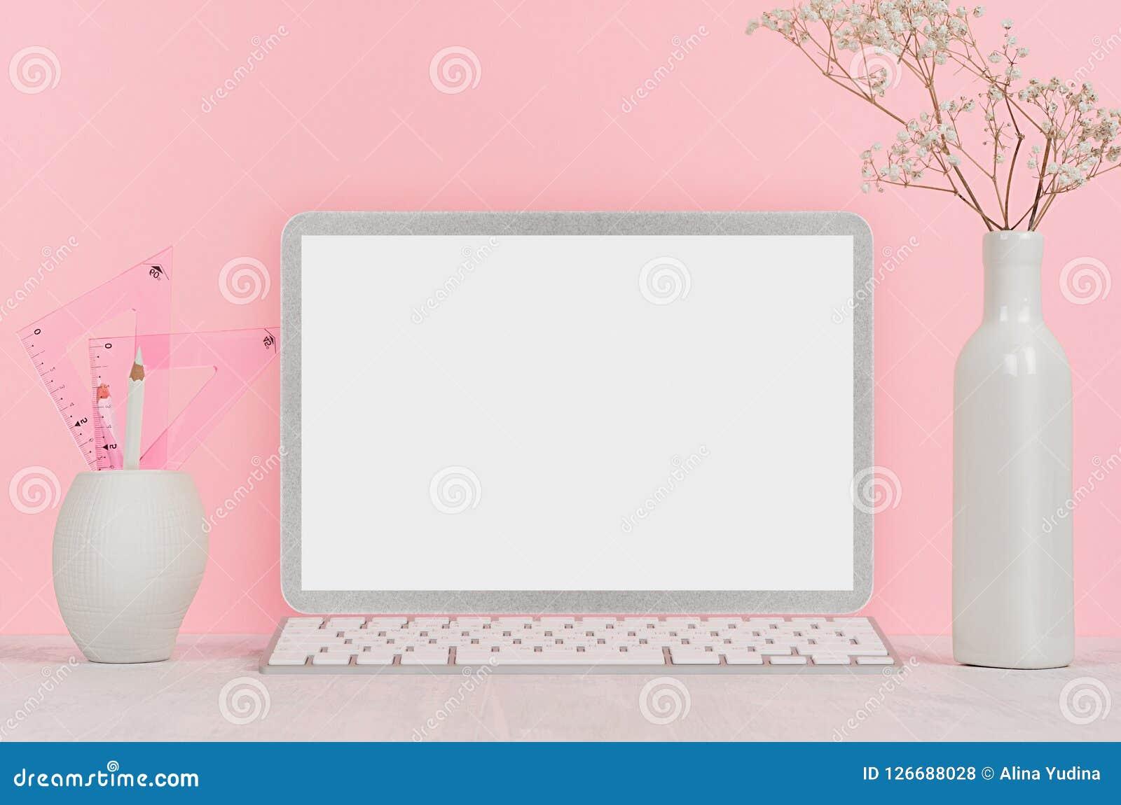 Elegant hem- arbetsplats med den stilfulla anteckningsboken för silvermellanrumsdator och vitbrevpapper, blommor i vas på rosa ba
