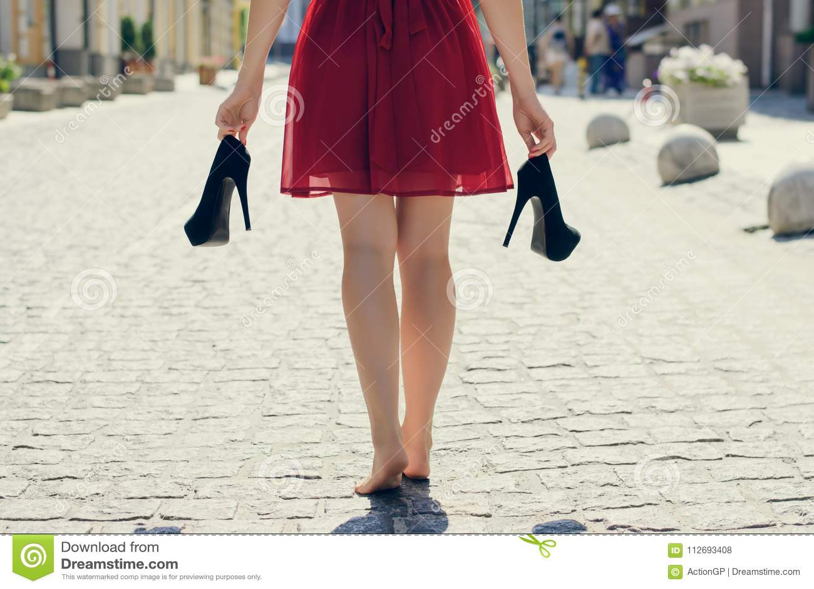 Elegant jong meisje in rode kleding met hoog-hielen in walkin handen,