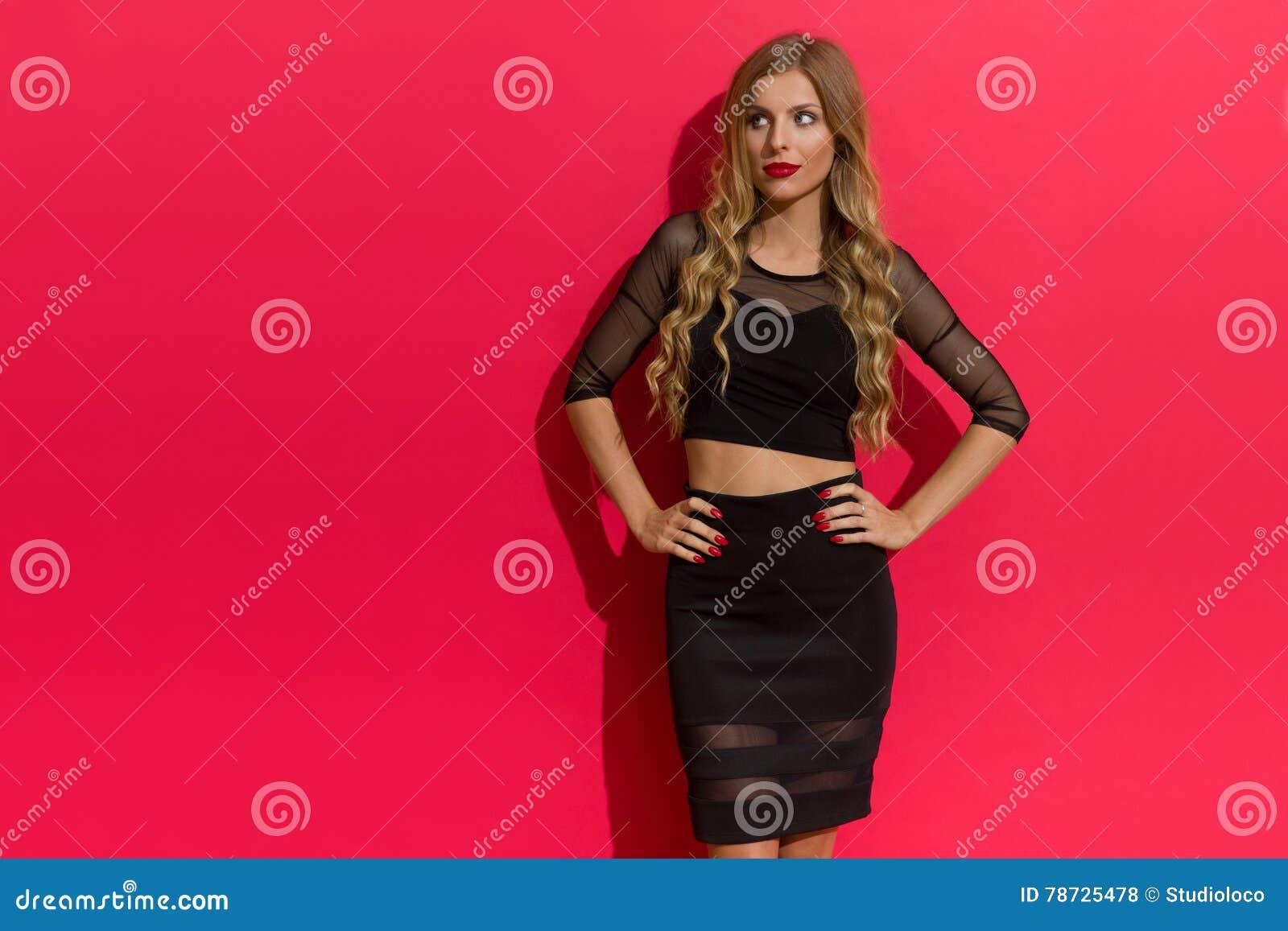 Elegant kvinna i den svarta klänningen som bort ser