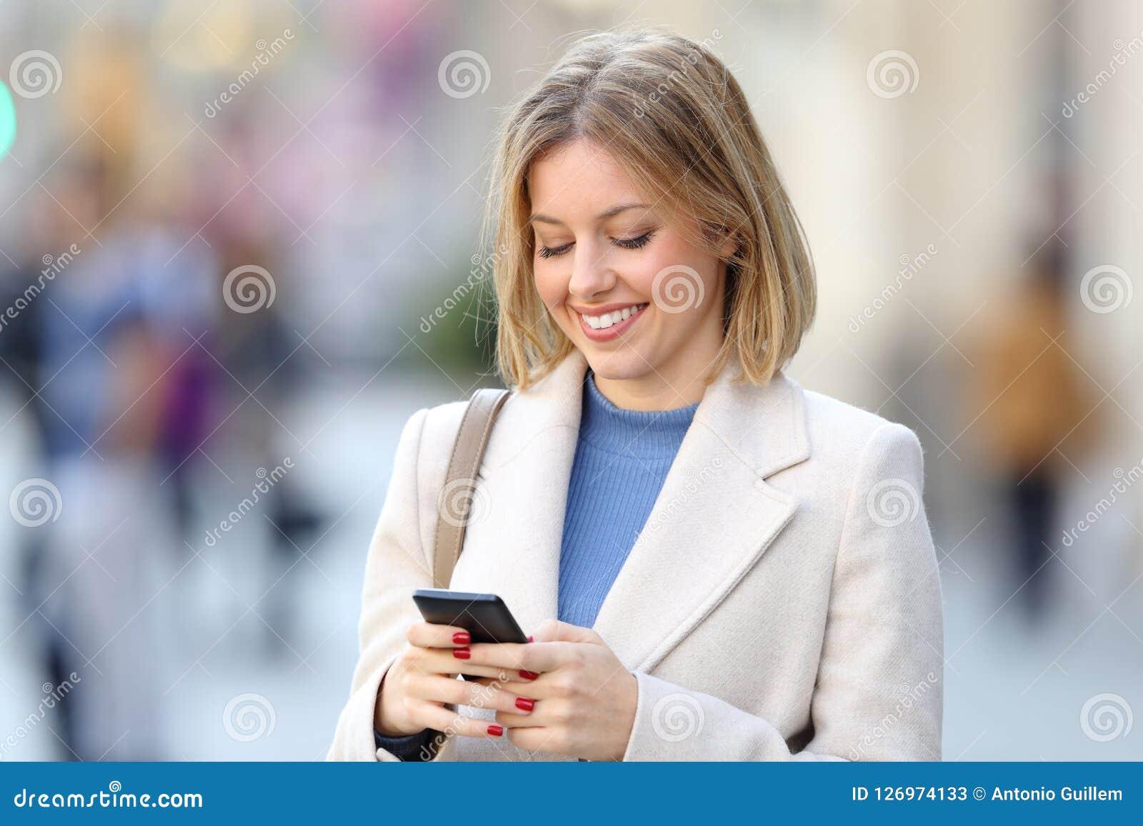 Elegant kvinna som använder en smart telefon på gatan